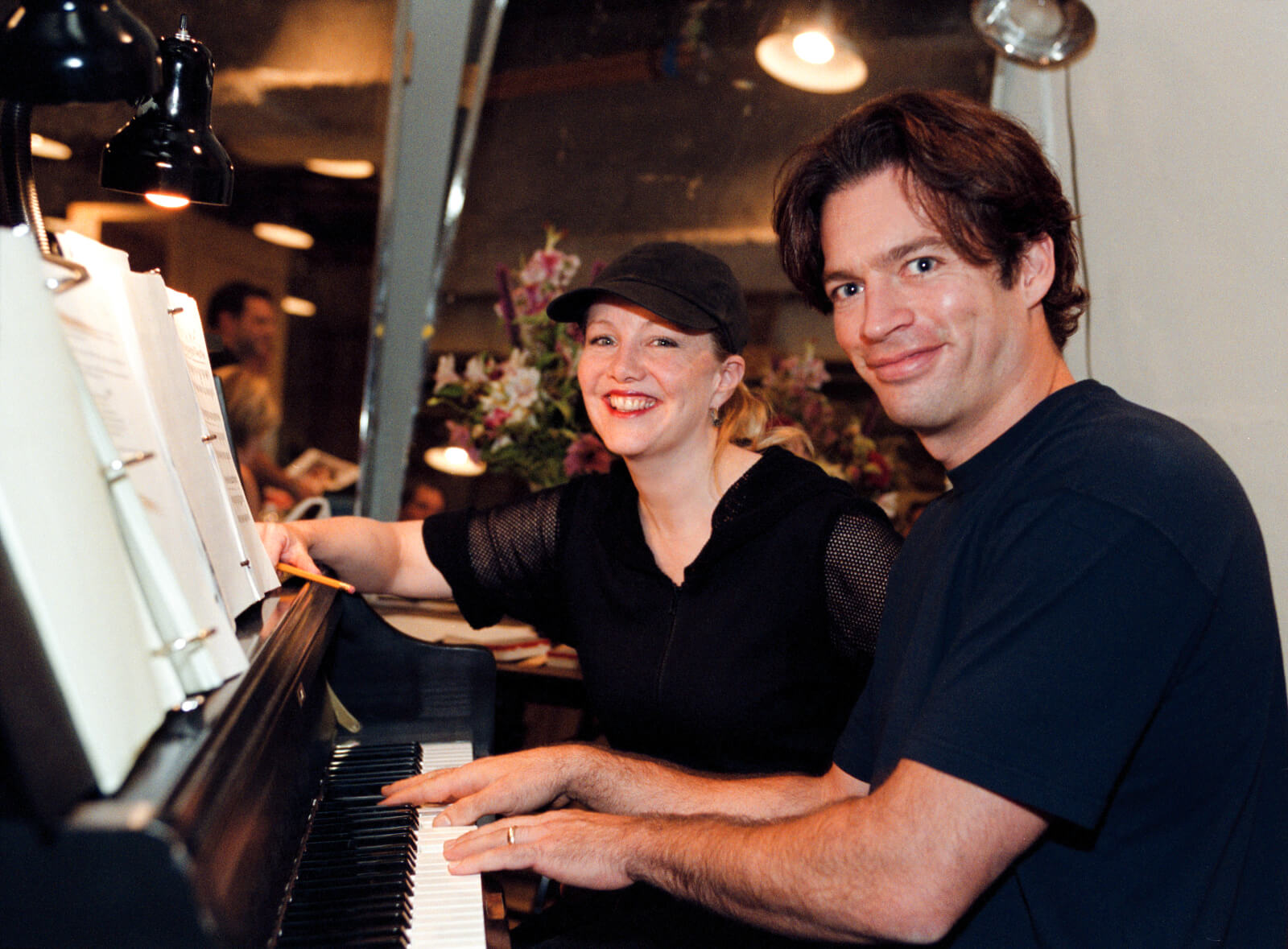 Susan Stroman and Harry Connick, Jr. sitting in a piano chair, working together.