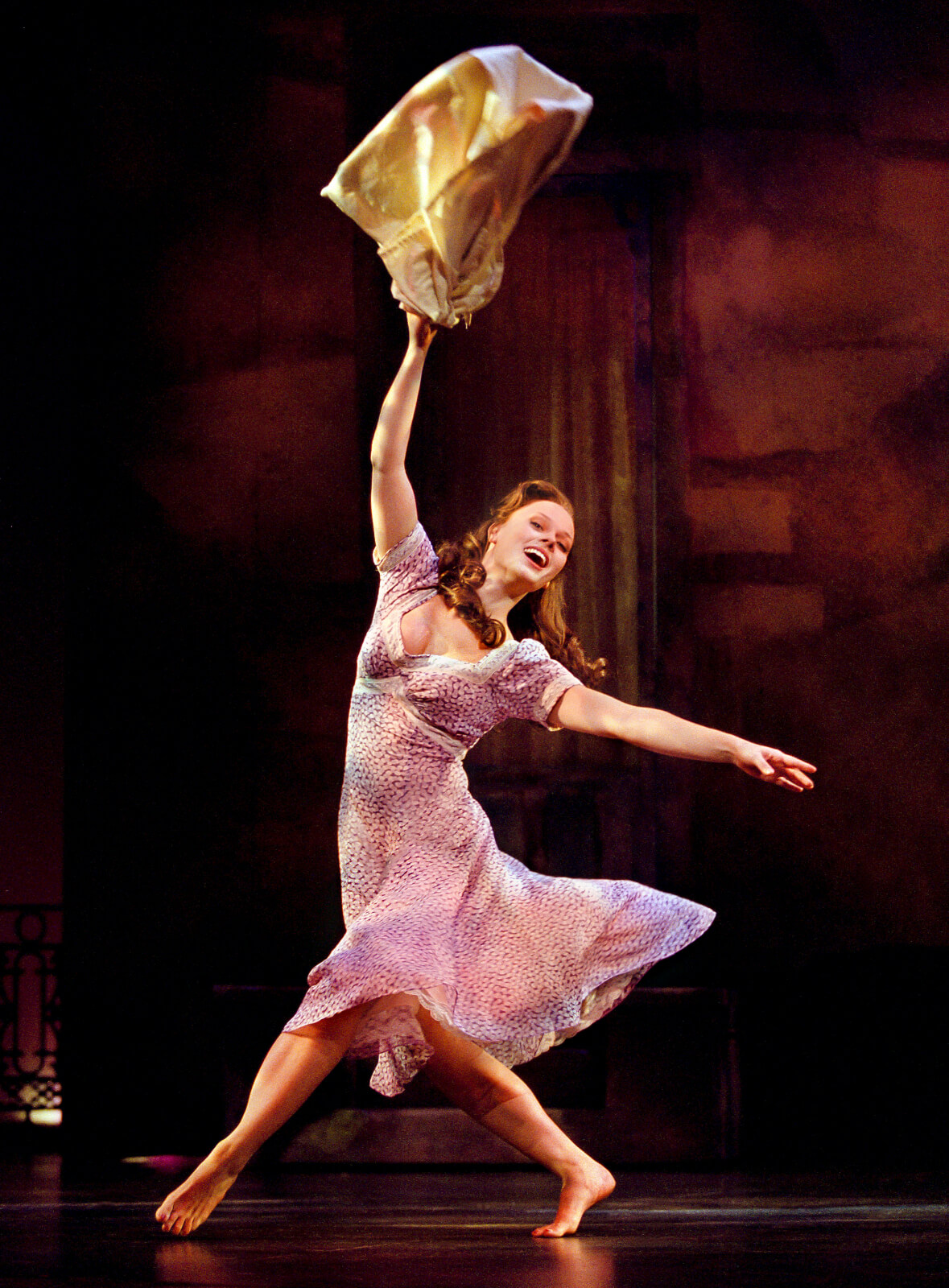 Therese Raquin (Kate Levering) all smiles, swinging her laundry.