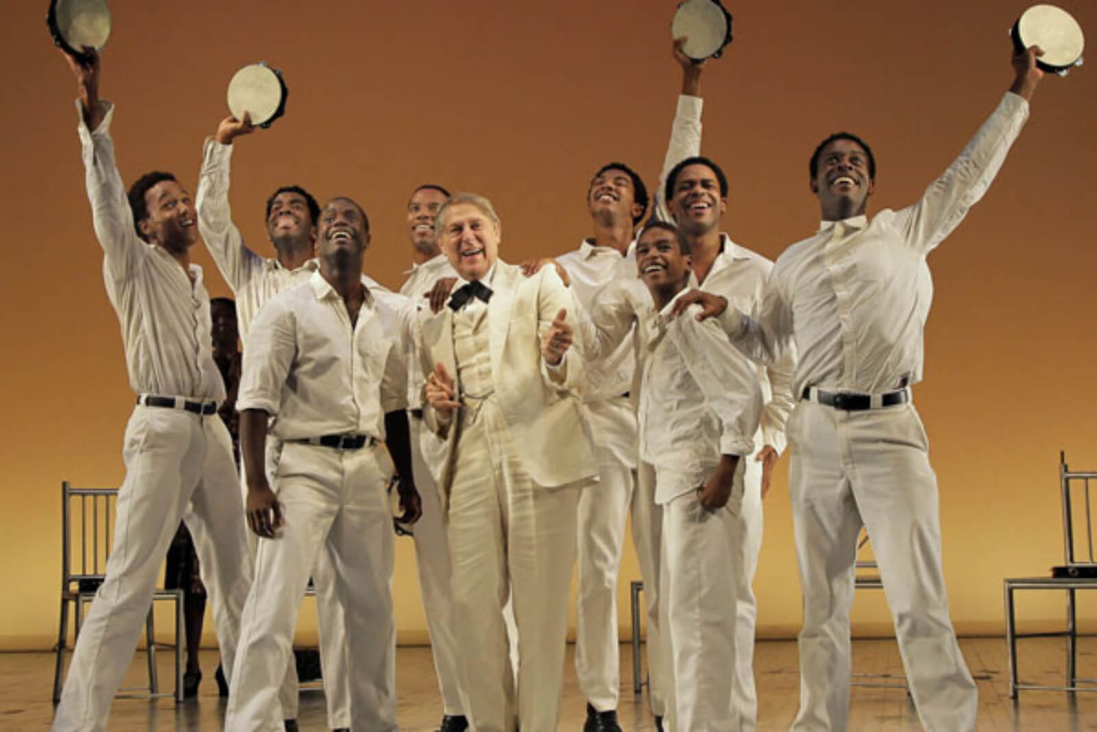 "Kendrick Jones, Julias Thomas III, James T. Lane, Rodney Hicks, John Cullum, Christian Dante White, Jeremy Gumbs, Derrick Cobey, and Josh Breckenridge are joyously singing ""Shout!"" They are all dressed in white."