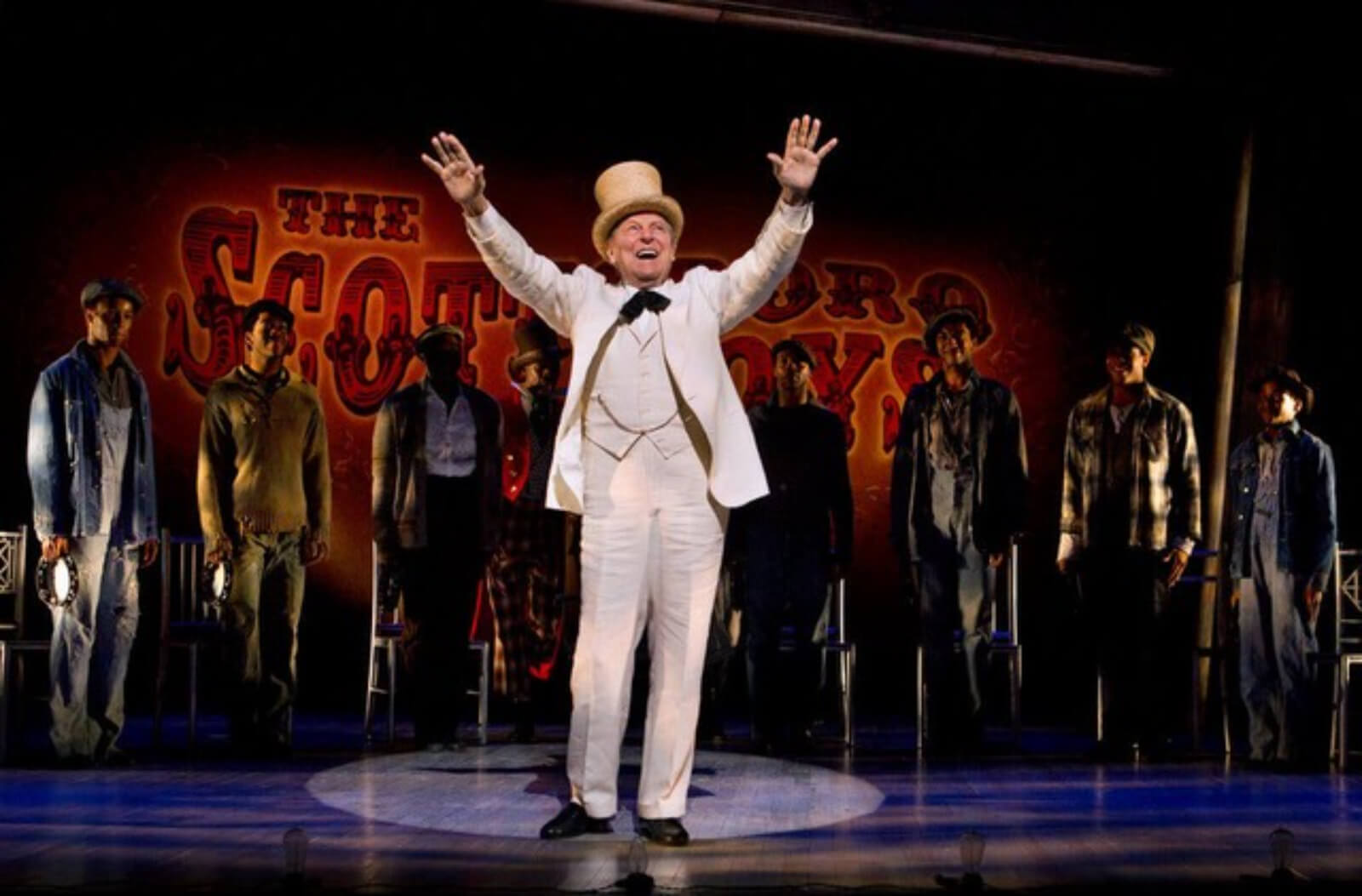 """The Interlocutor (John Cullum) is saying """"Gentleman be seated."""" He is wearing a white linen suit and a white top hat. He is in a hard edged spot. The Scottsboro Boys are in the background."""