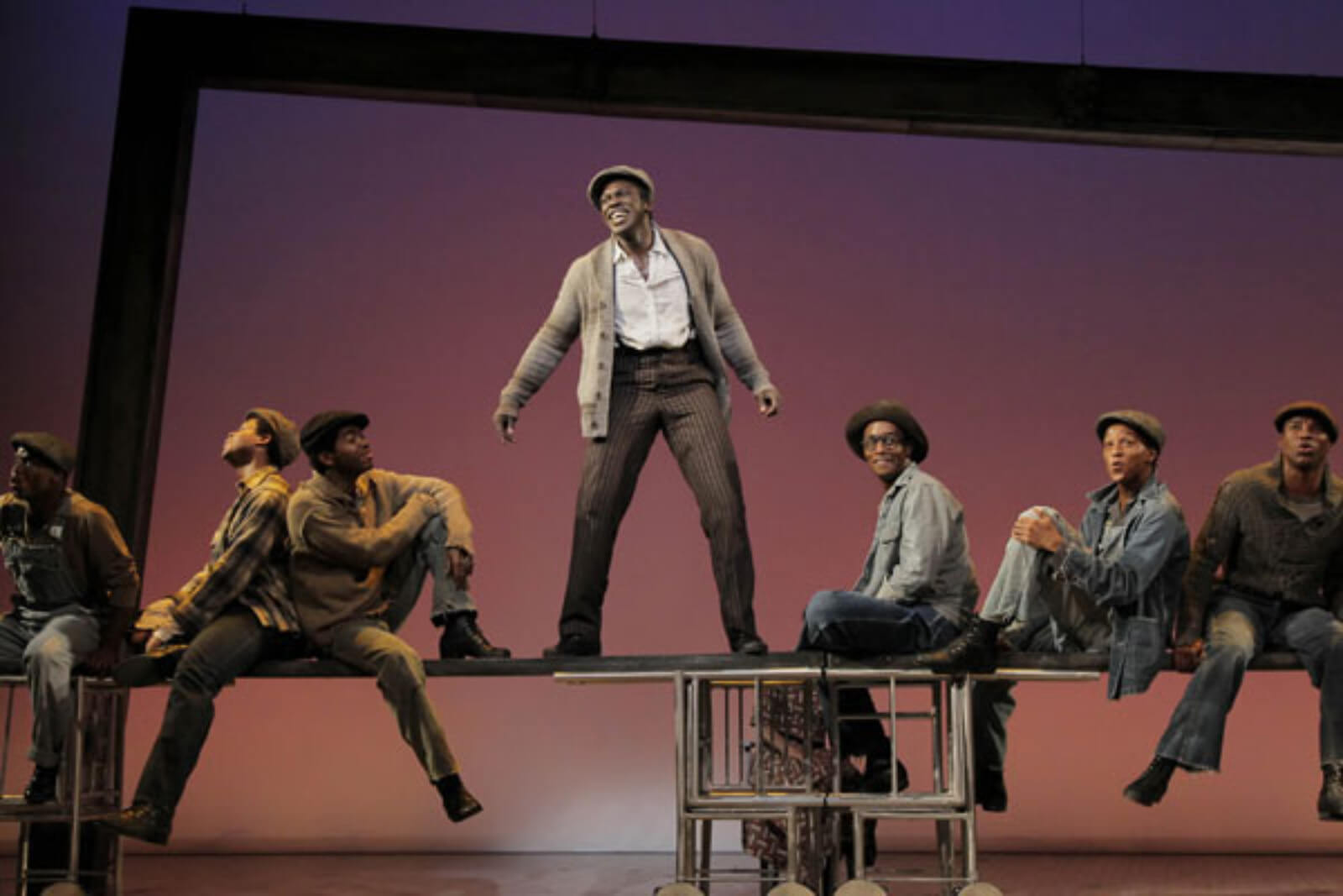 """Haywood Patterson (Joshua Henry) and the Scottsboro Boys sing """"Commencing in Chattanooga"""". They are balancing on beams that represent the top of a train. They are dressed in work clothes."""