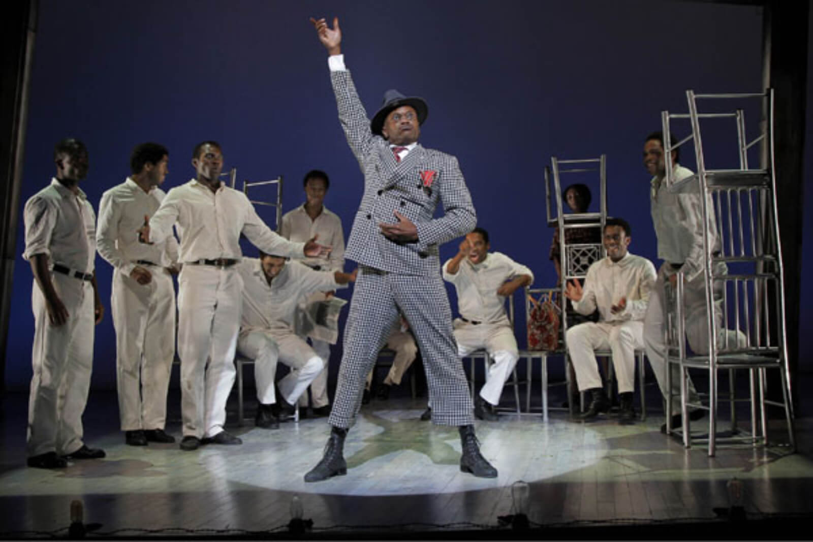 """Mr. Tambo (Forrest McClendon) sings """"Thats Not the Way We Do Things"""" surrounded by The Scottsboro Boys. He is playing the role of lawyer Sam Leibowitz. They are all in a jail cell."""