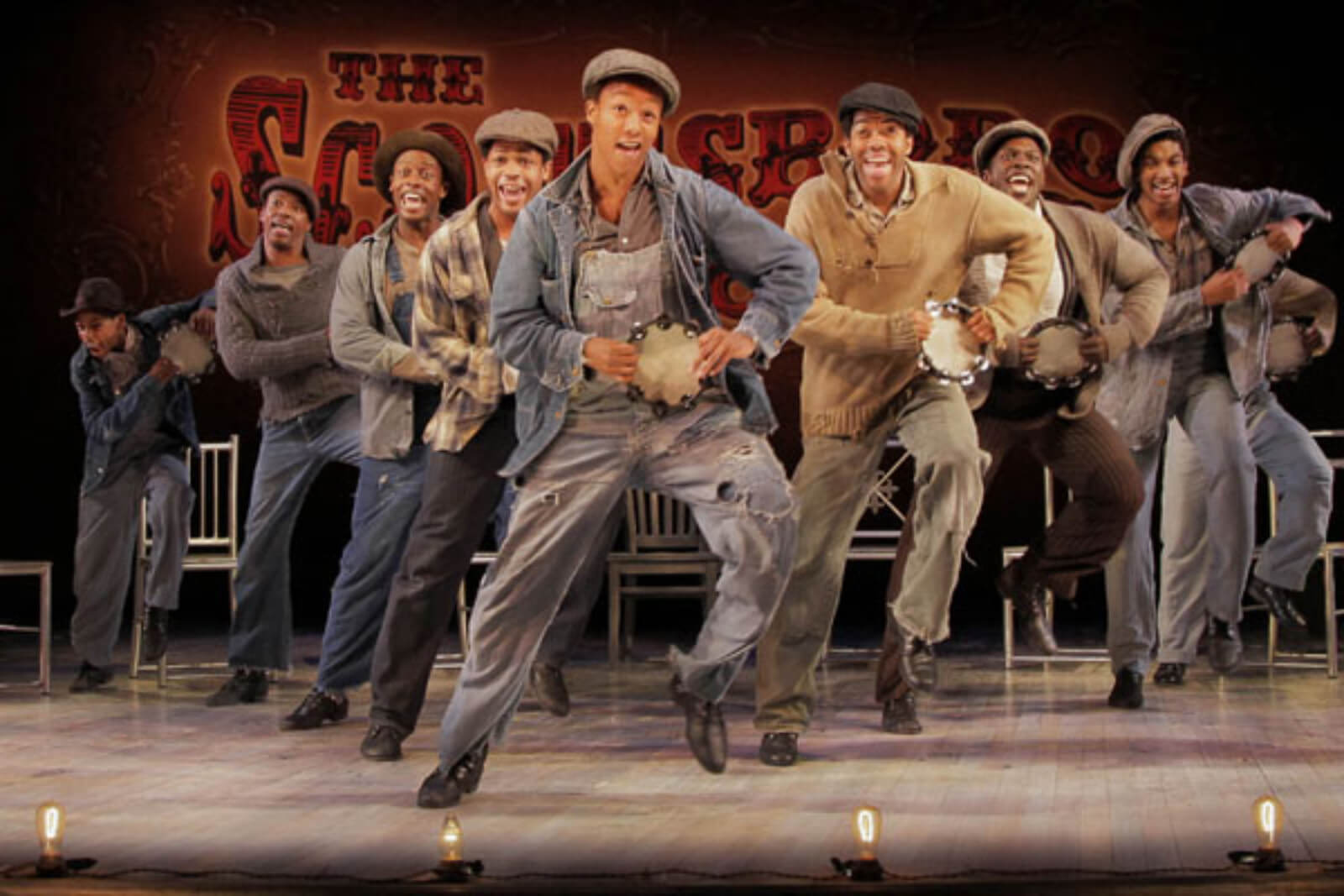 """The Scottsboro Boys sing and dance in """"Hey, Hey, Hey, Hey!"""" The actors are in a V-formation holding tambourines, doing a vaudeville flea hop step behind the footlights."""