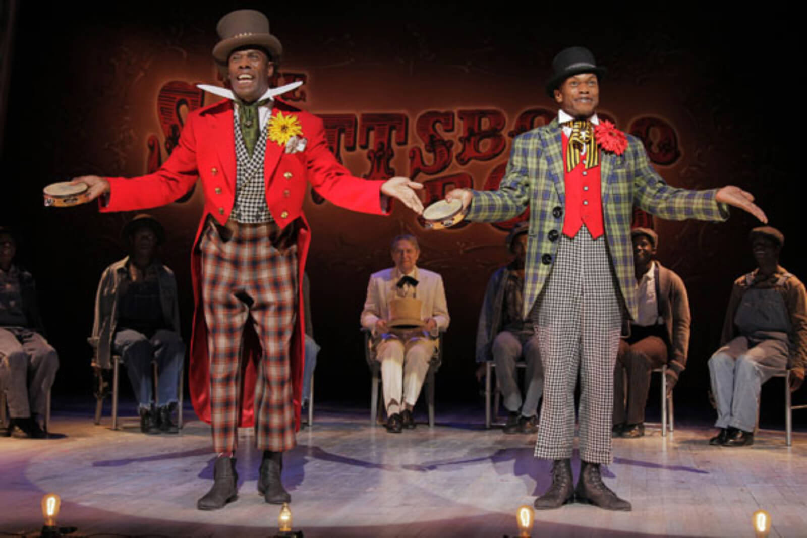 """Mr. Bones (Coleman Domingo) and Mr. Tambo (Forrest McClendon) singing """"Hey, Hey, Hey, Hey!"""" The title song in the show. They have tambourines in their hands and are wearing colorful costumes."""