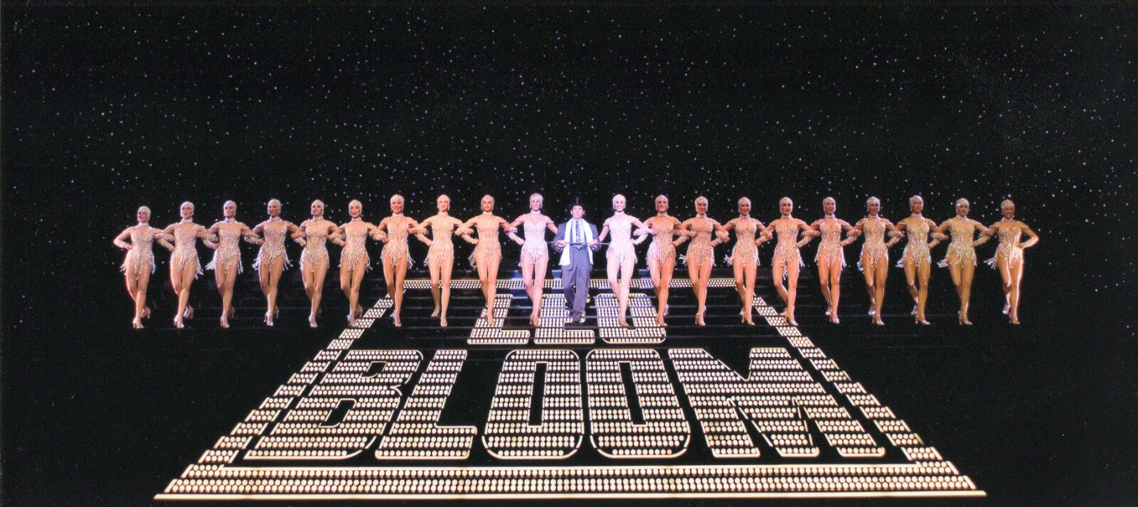 Leo Bloom (Matthew Broderick) and The Pearl Girls. They are walking down a large stair case with the word Leo Bloom painted in the center. There are 10 girls on each side of him. There is a star drop behind them.