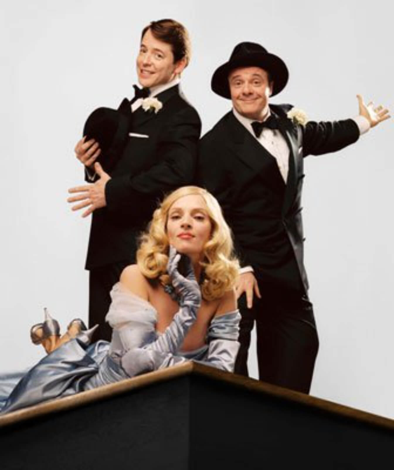 Leo Bloom (Matthew Broderick), Ulla (Uma Thurman) and Max Bialystock (Nathan Lane). They are posing with joy on top of the theatre.