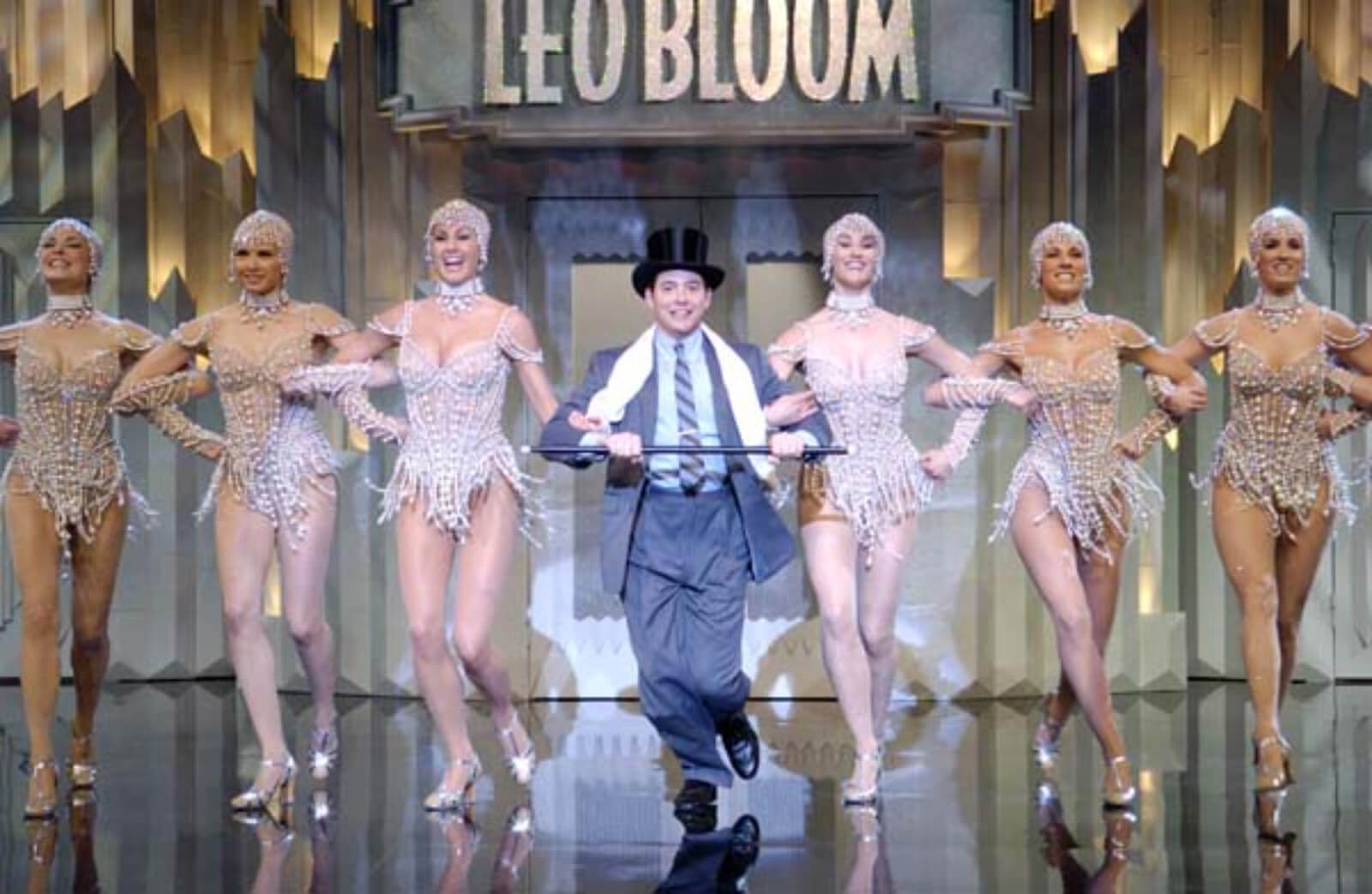 """Leo Bloom (Matthew Broderick) and the Pearl Girls dancing """"I Wanna Be a Producer"""". Leo dances with a top hat and cane. The girls are lined up on each side of him."""