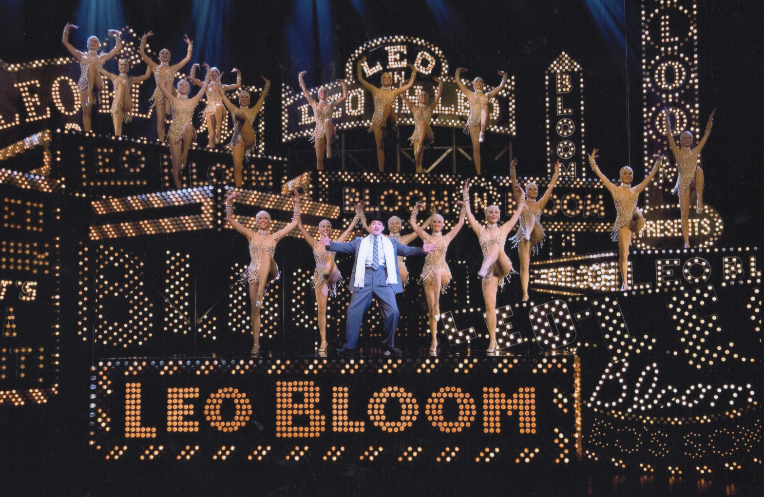 """Leo Bloom (Matthew Broderick) and the Pearl Girls dancing """"I Wanna Be a Producer"""". They are on a stage set with marquee lights saying Leo Bloom."""