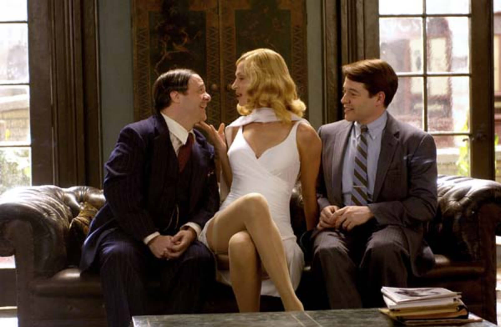 """Max Bialystock (Nathan Lane),Ulla (Uma Thurman) and Leo Bloom (Matthew Broderick) in """"When You Got It, Flaunt It"""". They are sitting on the sofa in Max's office. Ulla wears a tight white dress. They sit very close together. Max and Leo are smiling."""