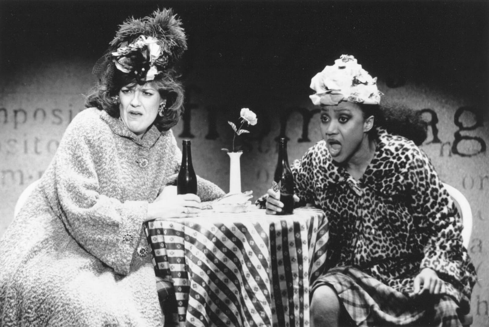 Karen Mason and Brenda Pressley sitting at a table in large hats and fur coats