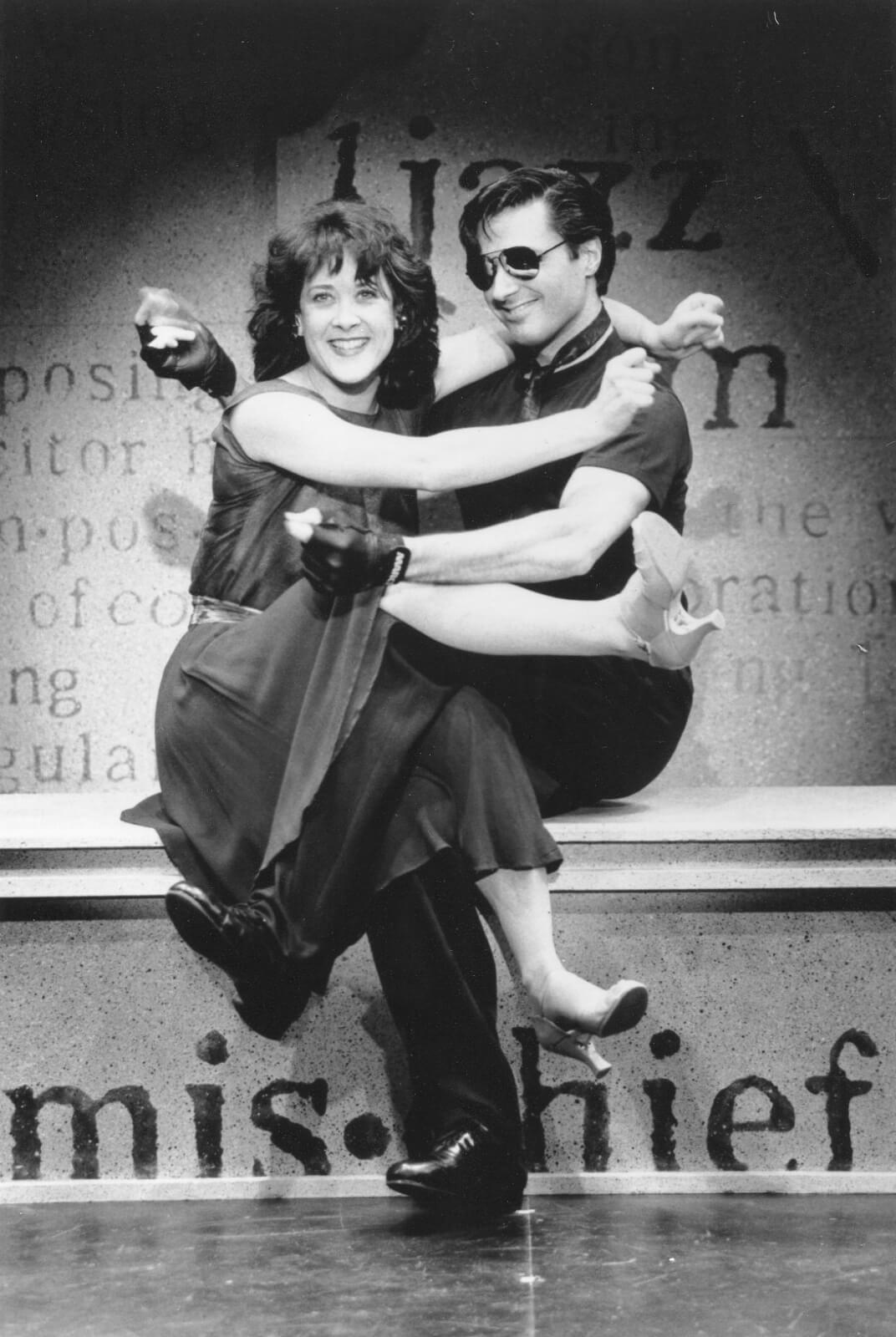"""Karen Ziemba and Robert Cuccioli performing """"Arthur in the Afternoon"""". They are sitting in a hugging position."""