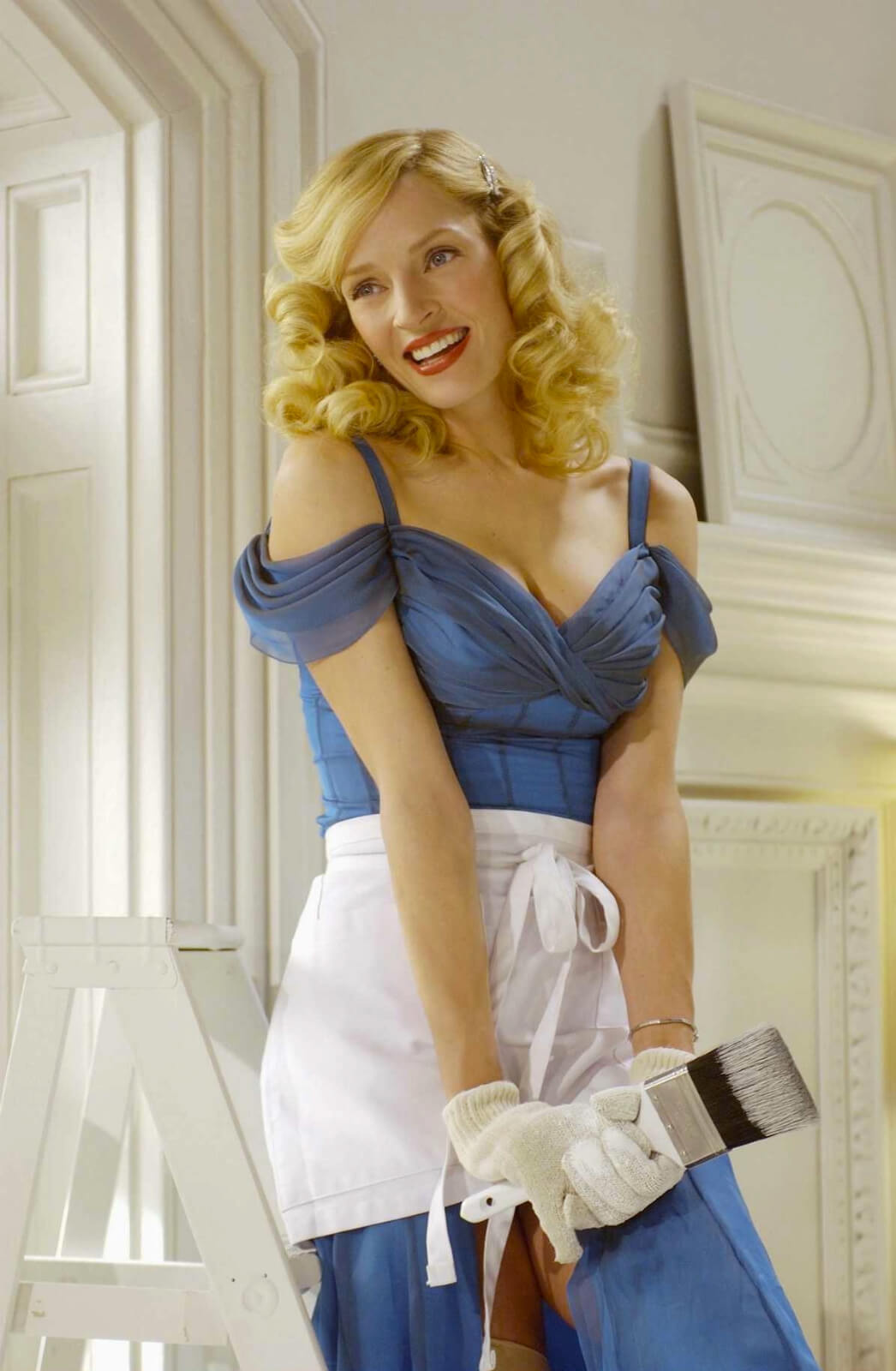 Ulla (Uma Thurman) in a blue dress, white gloves, and apron, holding a paintbrush while standing on a ladder. She has just painted Max's office totally white.