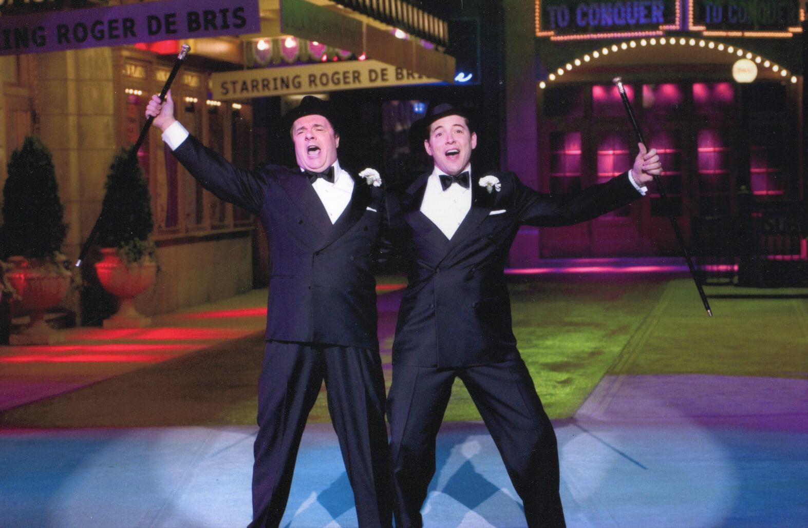 """Max Bialystock (Nathan Lane) and Leo Bloom (Matthew Broderick) singing """"Leo and Max"""". They are in Shubert Alley bathed in colored lights. They dance with fedoras and canes."""