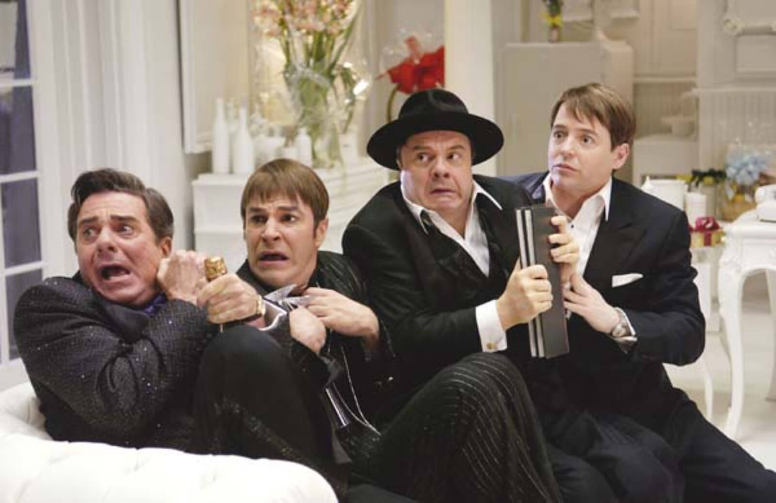 Roger De Bris (Gary Beach), Carmen Ghia (Roger Bart), Max Bialystock (Nathan Lane), and Leo Bloom (Matthew Broderick) sitting on a couch together looking startled at the entrance of Franz Liebkind.