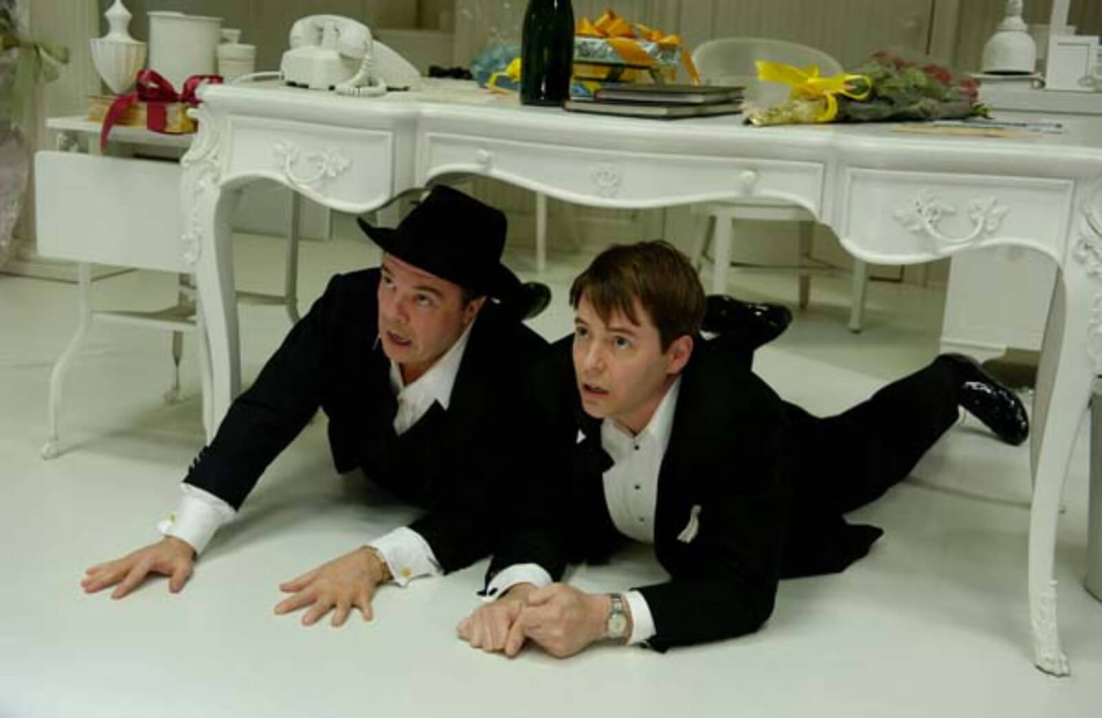 Max Bialystock (Nathan Lane) and Leo Bloom (Matthew Broderick) hiding under the desk.