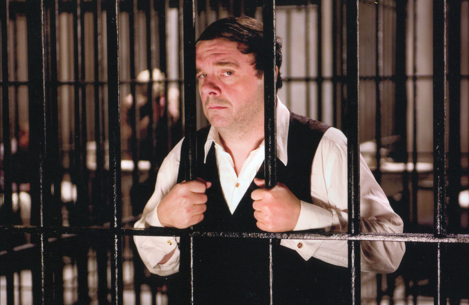 """Max Bialystock (Nathan Lane) looking very disappointed behind bars. He is singing """"Betrayed""""."""