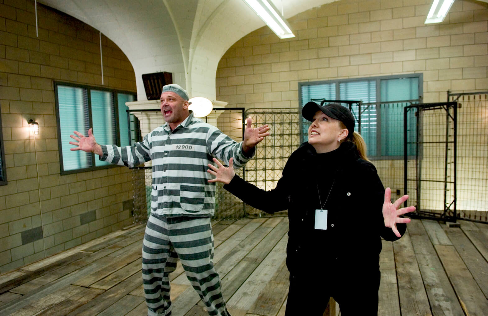 """Susan Stroman and jailbird Brian Rogalski rehearsing """"Prisoners of Love"""". Stro is directing Brian on how to deliver the song. Brian is dressed in a jail striped uniform."""