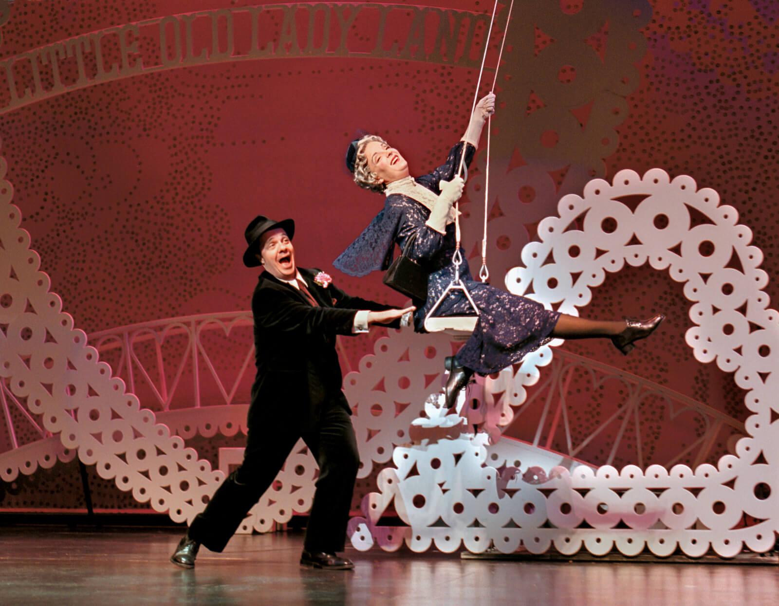 Max Bialystock (Nathan Lane) pushing Lick-me Bite-me (Jennifer Smith) in a swing.