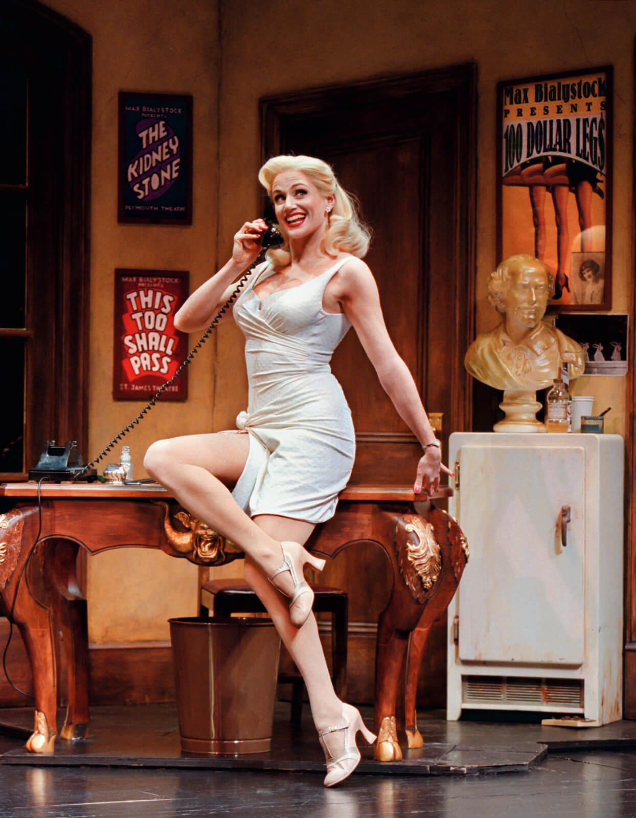 Ulla (Cady Huffman) answering the telephone sitting on a desk.