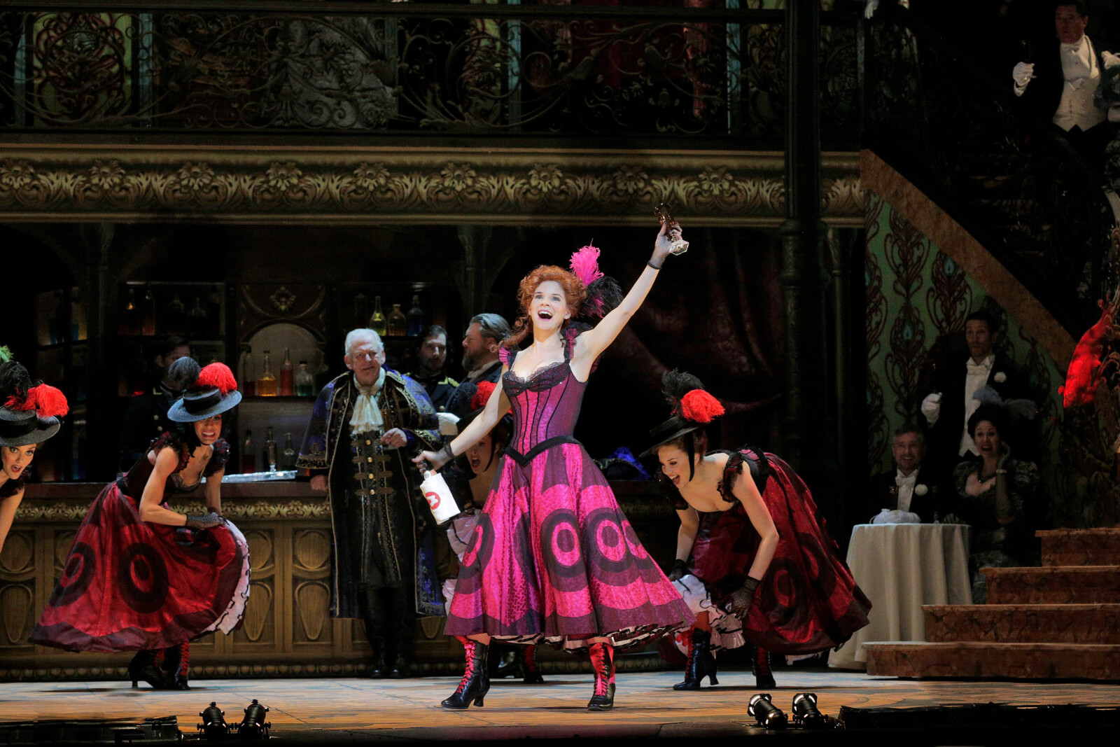 """Valencienne (Kelli O'Hara) performing """"We're the Ladies of the Chorus"""". She is in a Magenta Can Can dress singing with a bottle of wine."""
