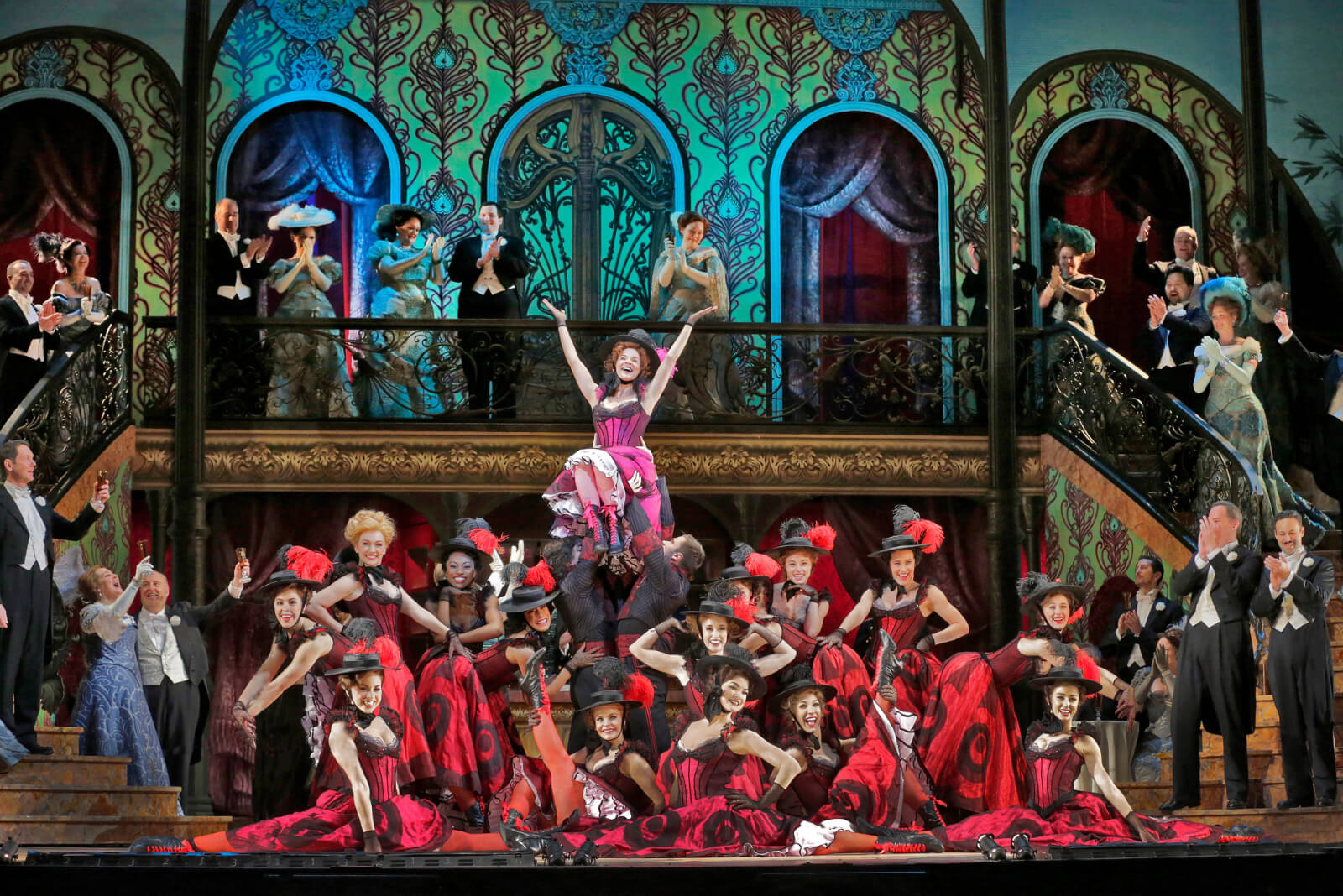 Valencienne (Kelli O'Hara) dances with the Grisettes at Chez Maxime. Kelli is dressed in a Magenta Can Can dress and the Grisettes are dressed in Red Can Can dresses.