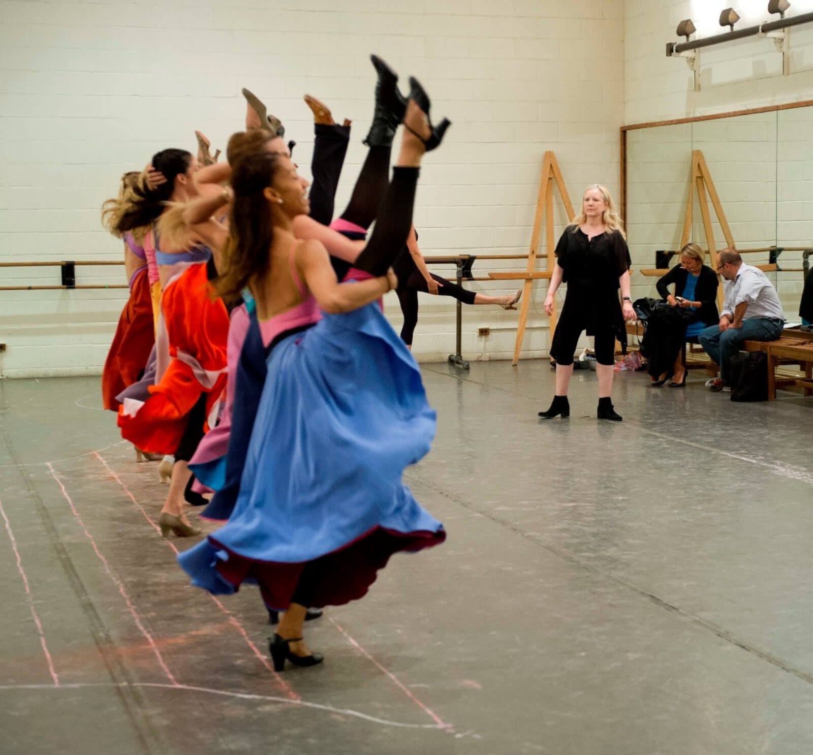 """Susan Stroman with the Female dancers rehearsing the """"Can Can"""". The ladies stand in a line kicking with one leg high in the air."""