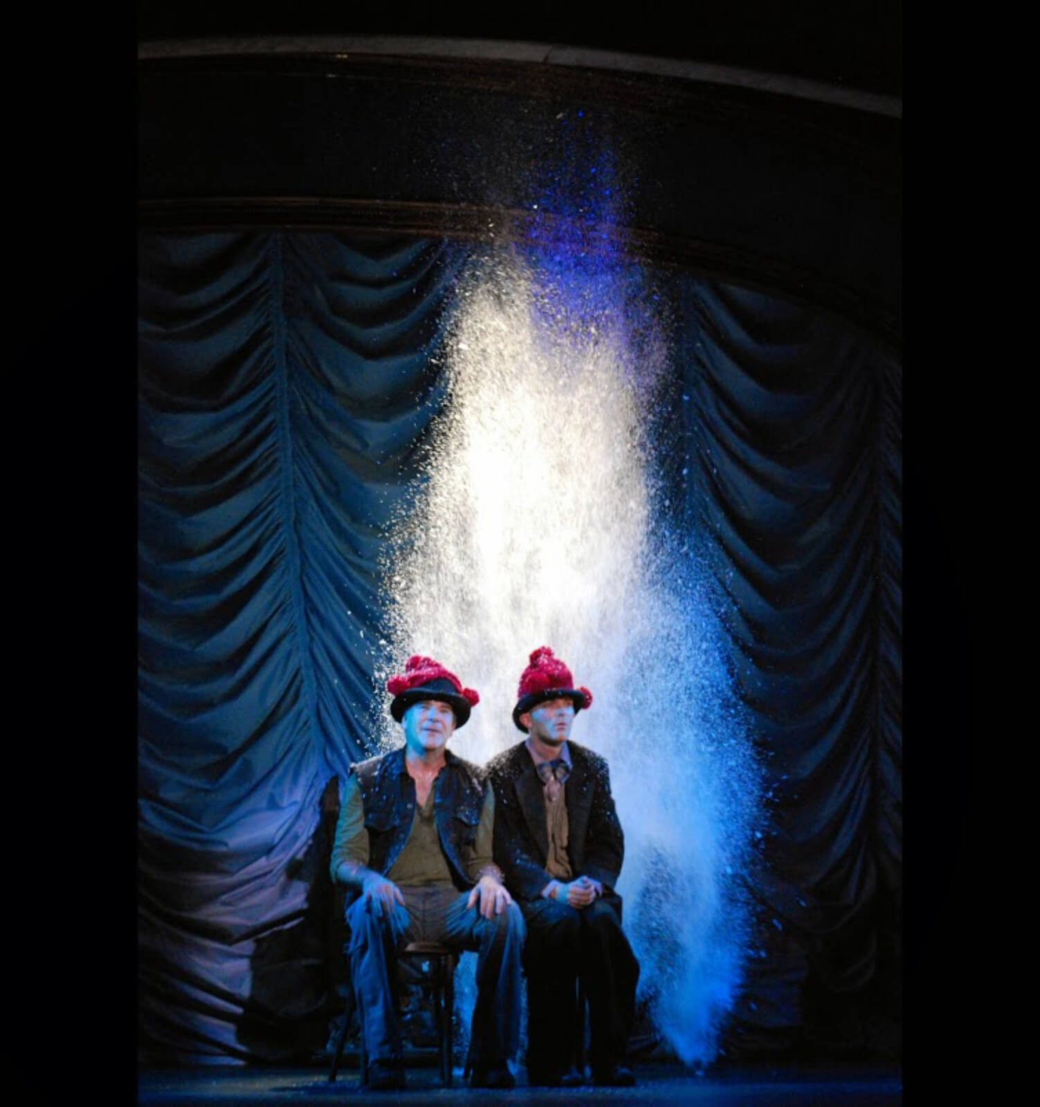 """Mandy Patinkin and Taylor Mac singing """"Snow"""". They are sitting close together with red wool hats on and a large amount of snow is falling from above."""