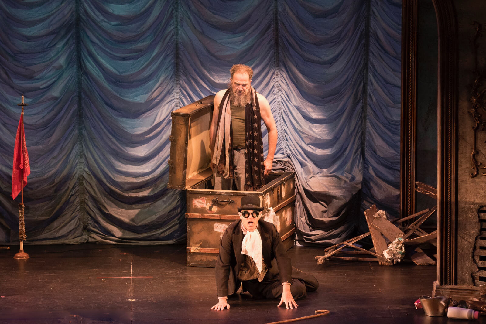 Mandy Patinkin and Taylor Mac in a scene from The Last Two People on Earth: An Apocalyptic Vaudeville. Mandy comes out of a trunk while Taylor sits on the floor, looking terrified.