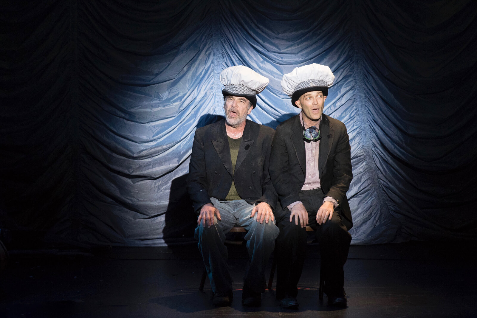 """Mandy Patinkin and Taylor Mac singing """"Making Pies"""". They are wearing bakers hats on top of their derby hats."""