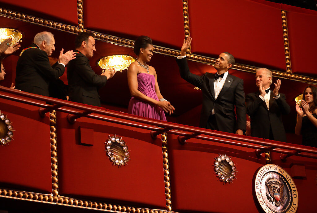President Barack Obama waving to the Kennedy Center Awards Honorees with Michelle Obama.