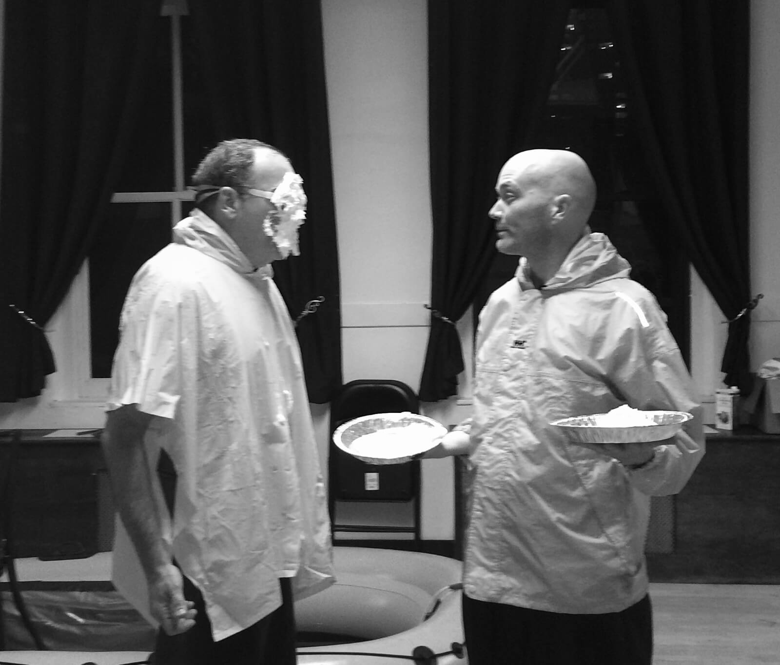 Mandy Patinkin and Taylor Mac rehearsing a scene with pies. Mandy has face covered in whipped cream while Taylor holds the empty pie plate.