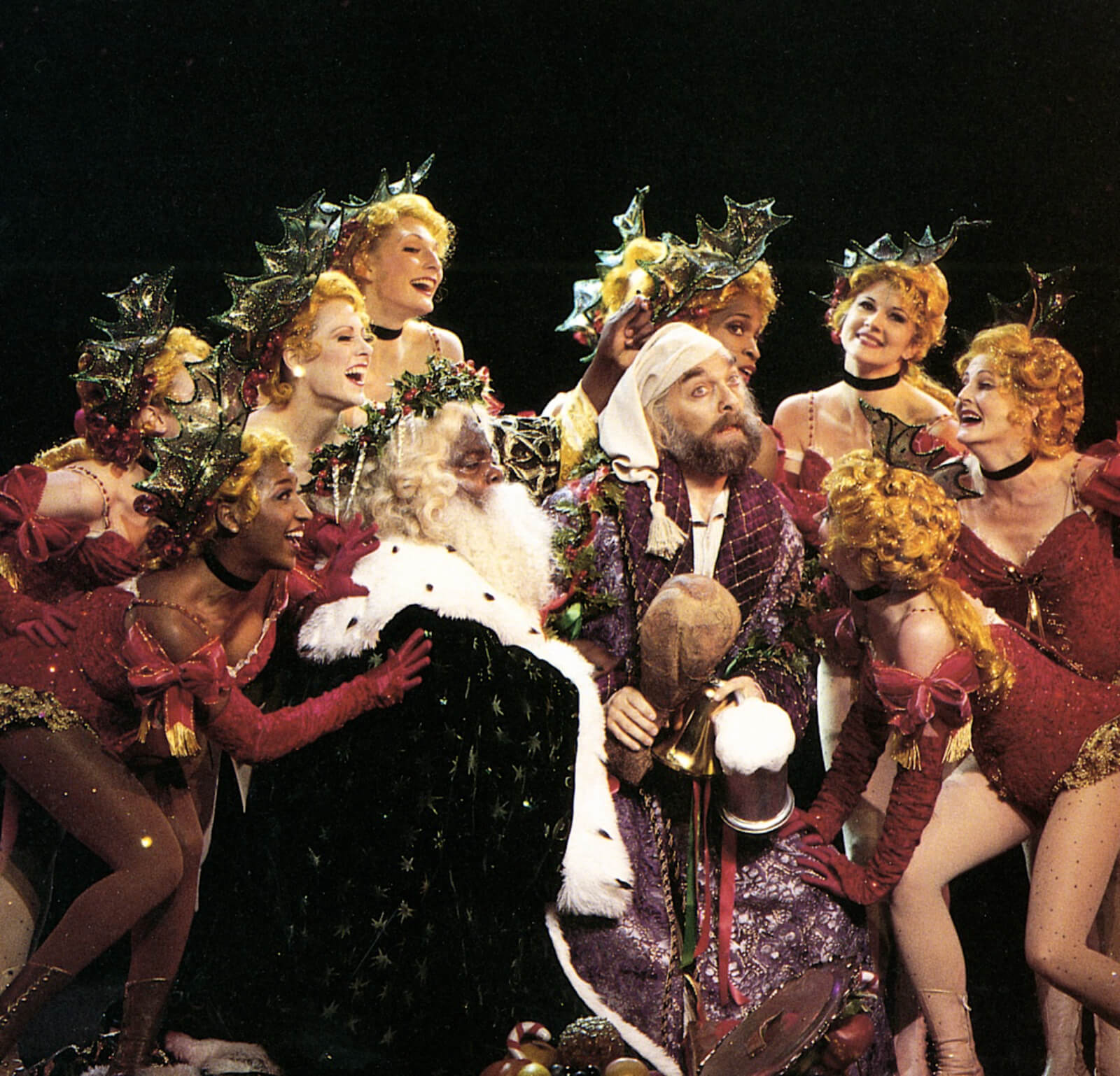 """The Holly Girls gather around Scrooge (Walter Charles)and The Ghost of Christmas Present (Michael Mandell) in """"Abundance and Charity""""."""