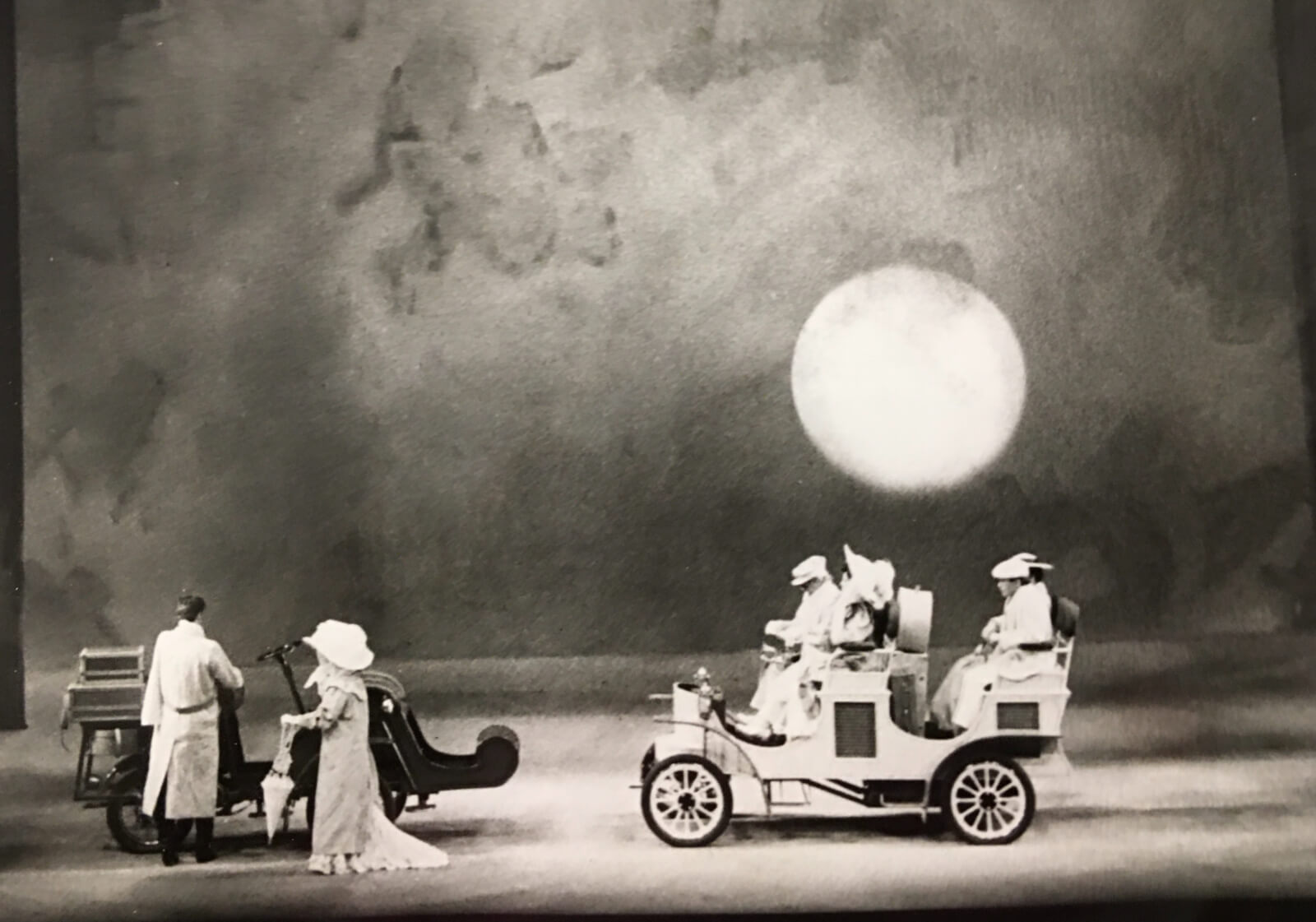 """Michael Anania's set for """"Night Waltz 2"""". The sun sits low. There are two couples arriving in cars."""