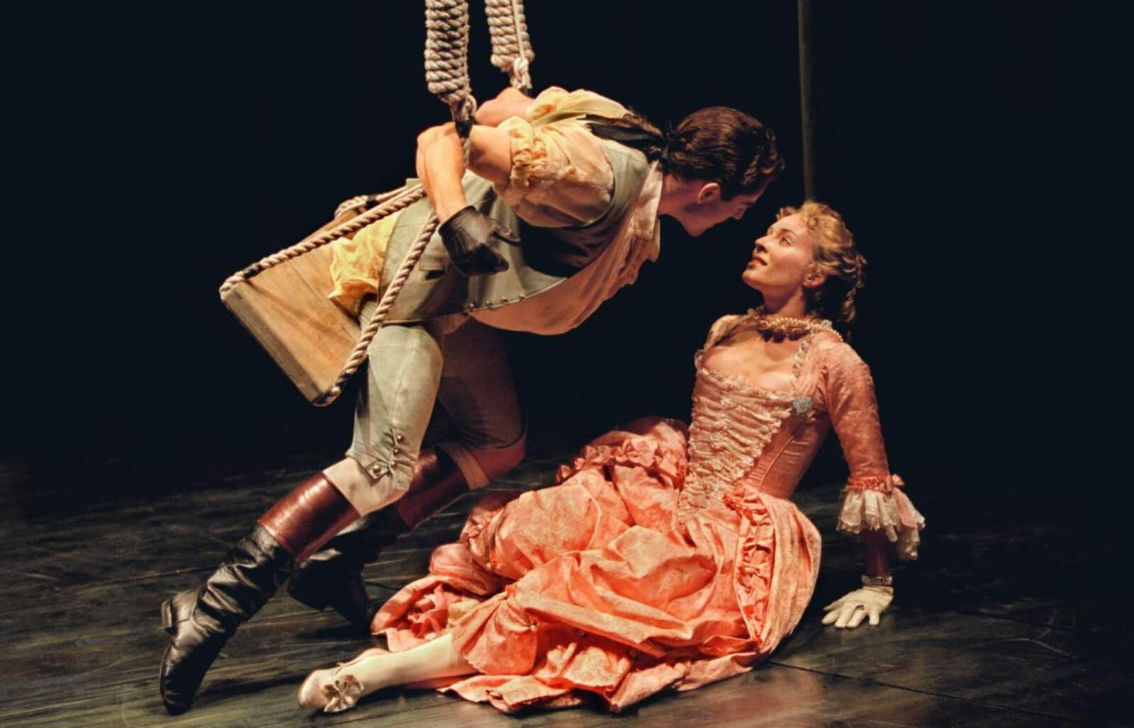 """Seán Martin Hingston and Stephanie Michels in """"Swinging"""" from Contact. He is leaning in for a kiss, she is on the ground. They are both dressed in costumes from the famous Fragonard Painting The Swing."""