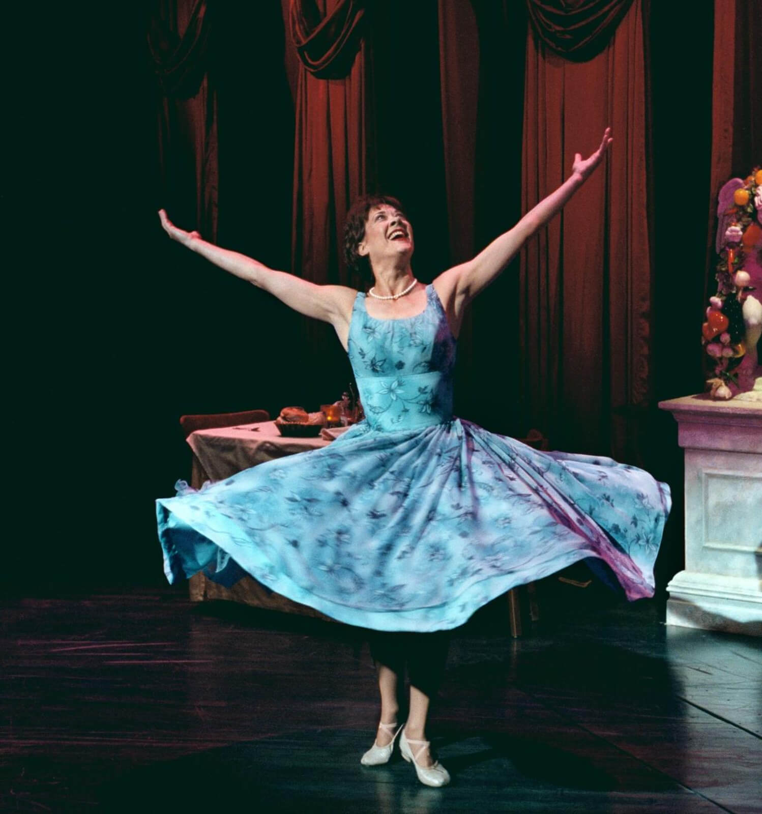 Wife (Karen Ziemba) twirling with her arms up in a restaurant. She is wearing a beautiful blue dress in Contact.