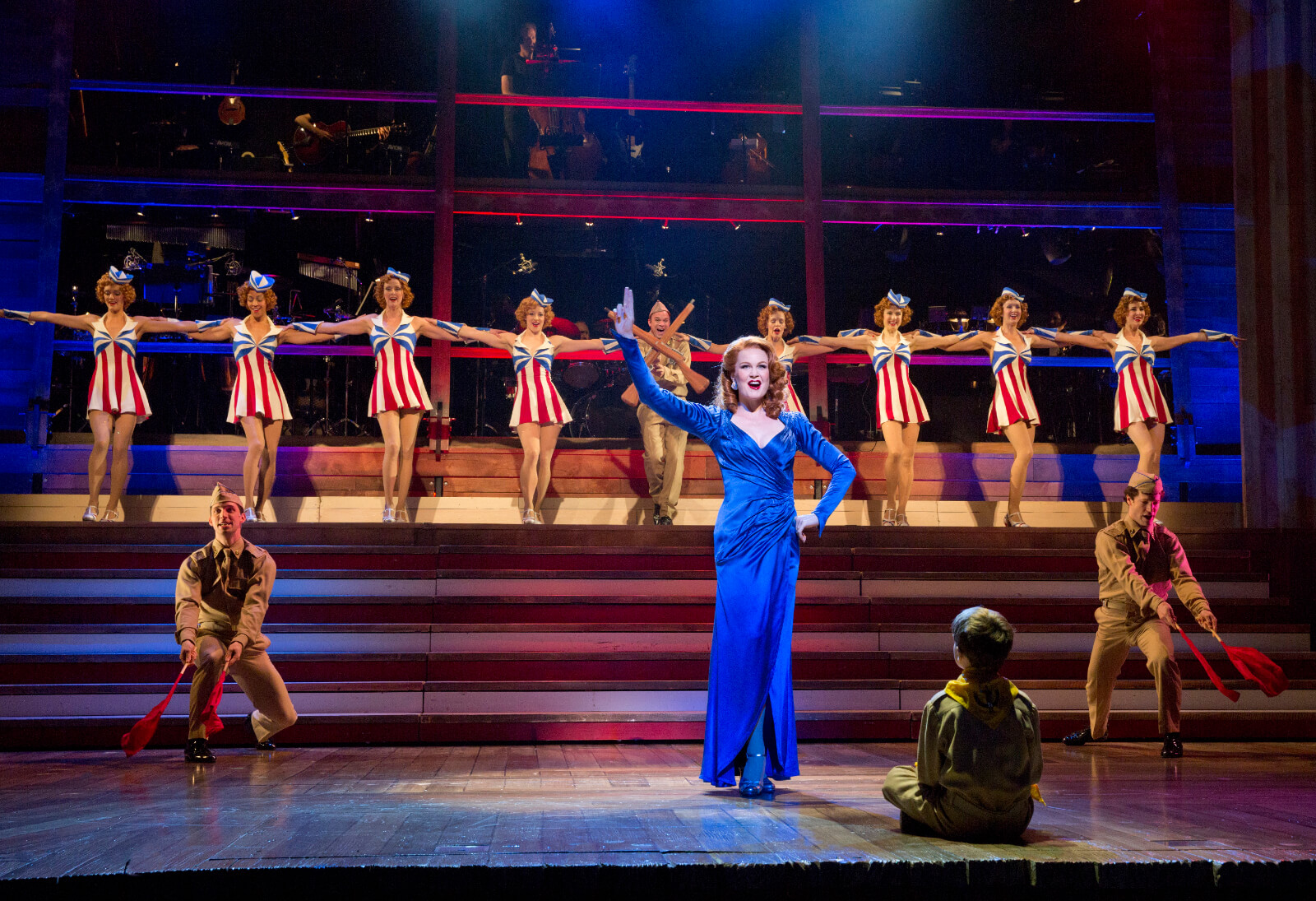 Sandra Bloom (Kate Baldwin) performs in a blue dress as part of the USO as Young Will (Zachary Unger) sits in front of her.