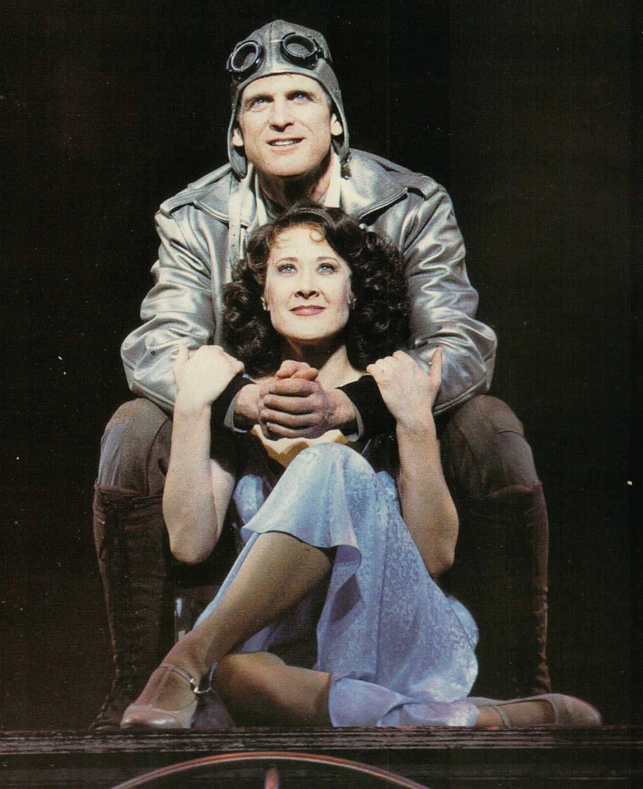 "Bill Kelly (Daniel McDonald) in a pilot suit, embracing Rita Racine (Karen Ziemba) from behind. Rita holding his arms singing ""First You Dream""."