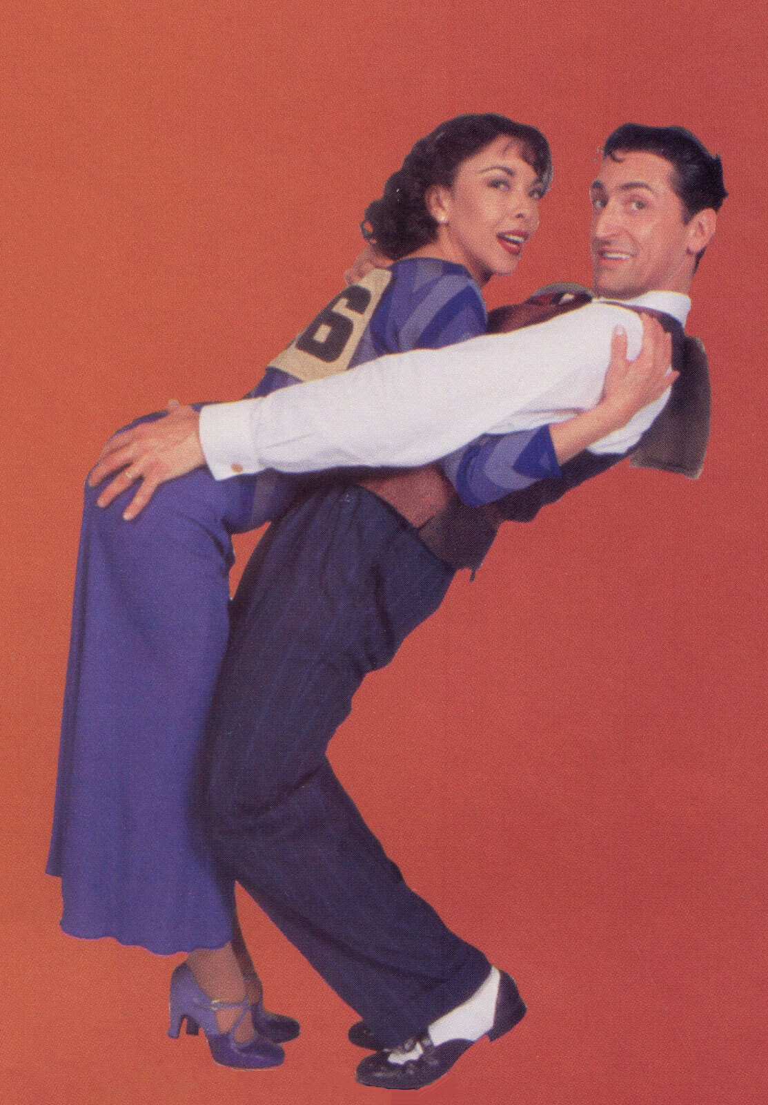 A Flying Dunlap/Couple #46 (JoAnn M. Hunter) in a matching purple outfit and Sonny (Gregory Mitchell) looking dapper in a suit, touching the former's backside, during a photoshoot.