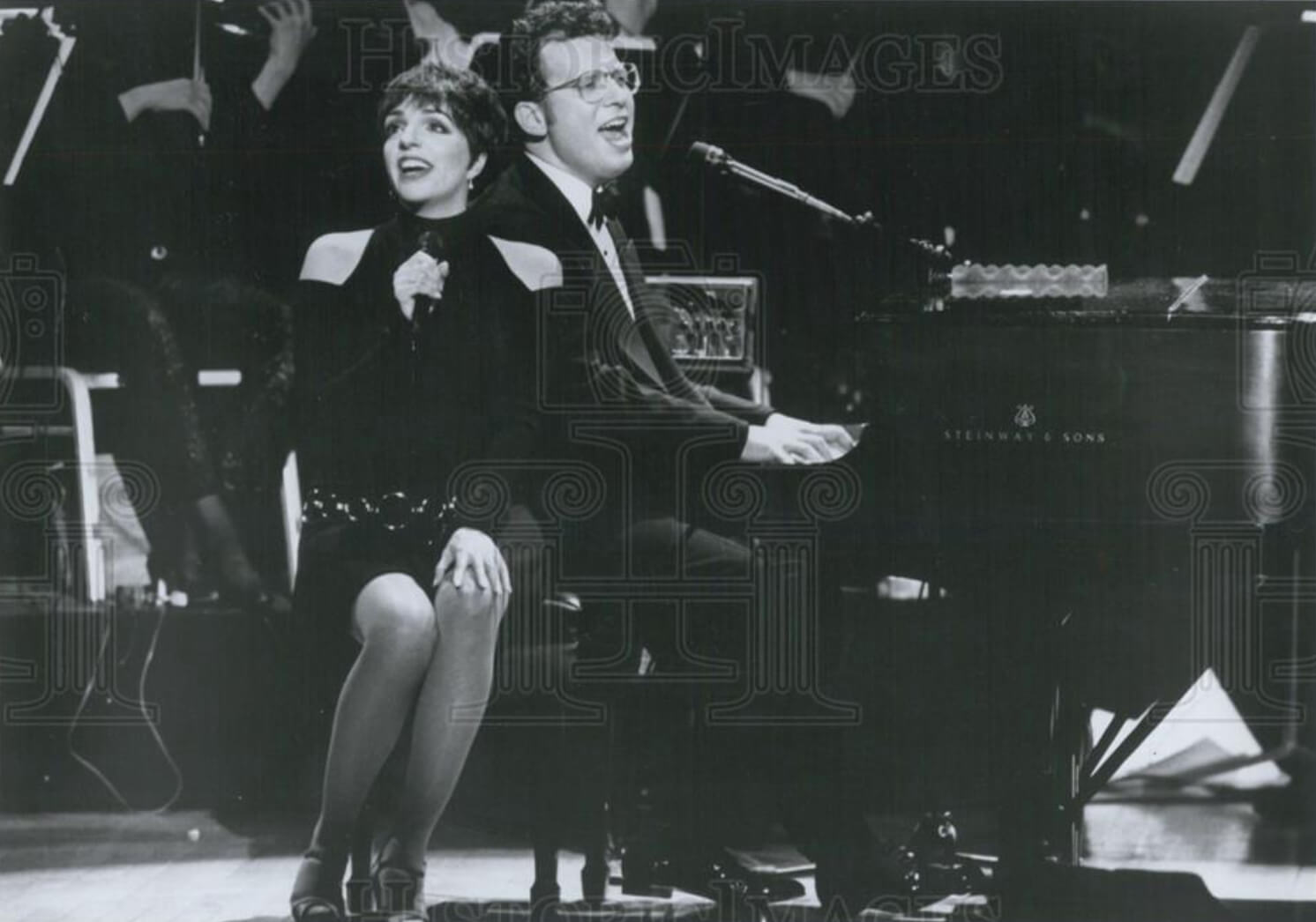A black and white photo of Liza Minnelli singing with Billy Stritch beside the piano.