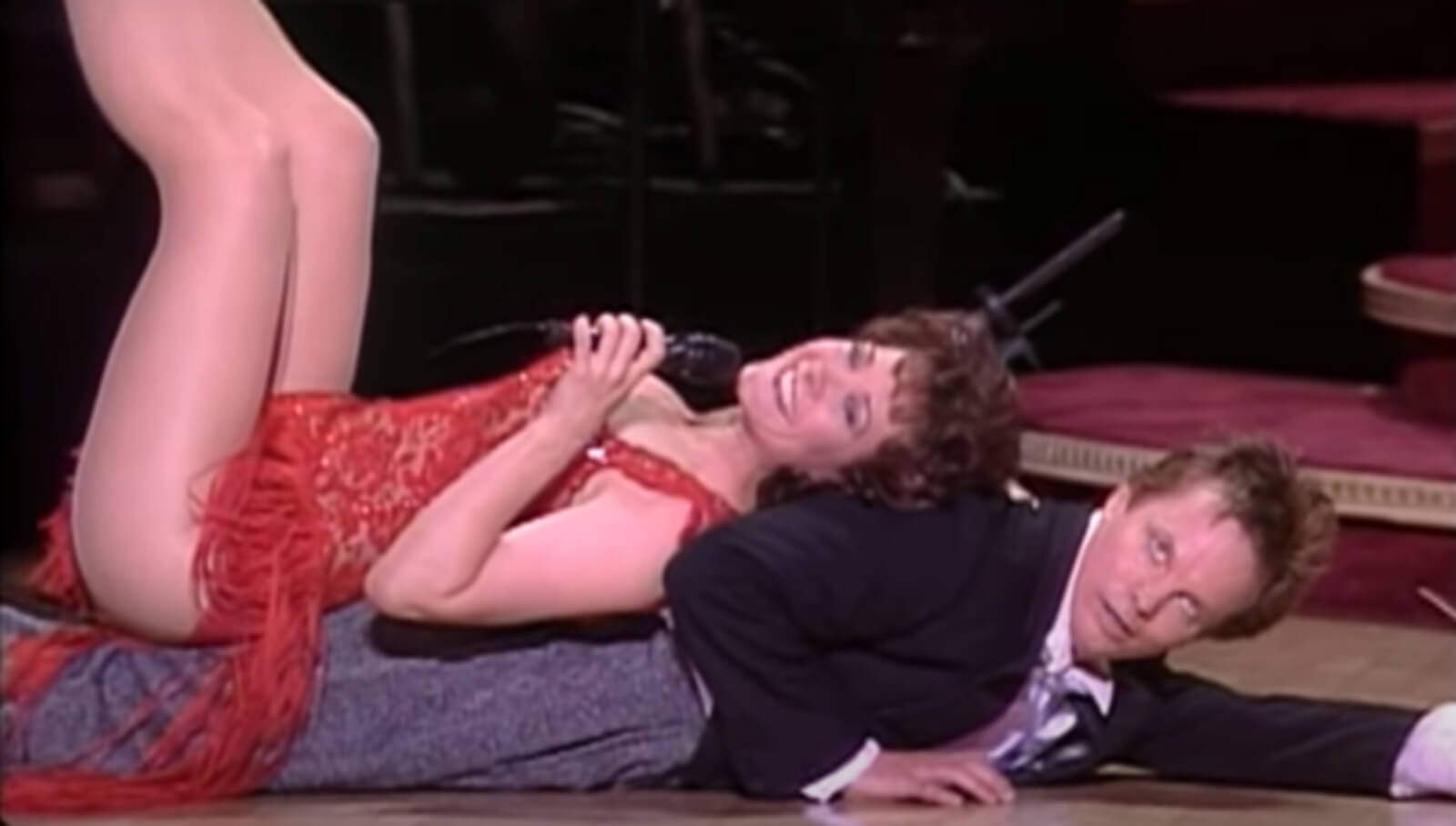 Karen Ziemba in a beautiful red dress sings with her back on Bill Irwin on the floor.
