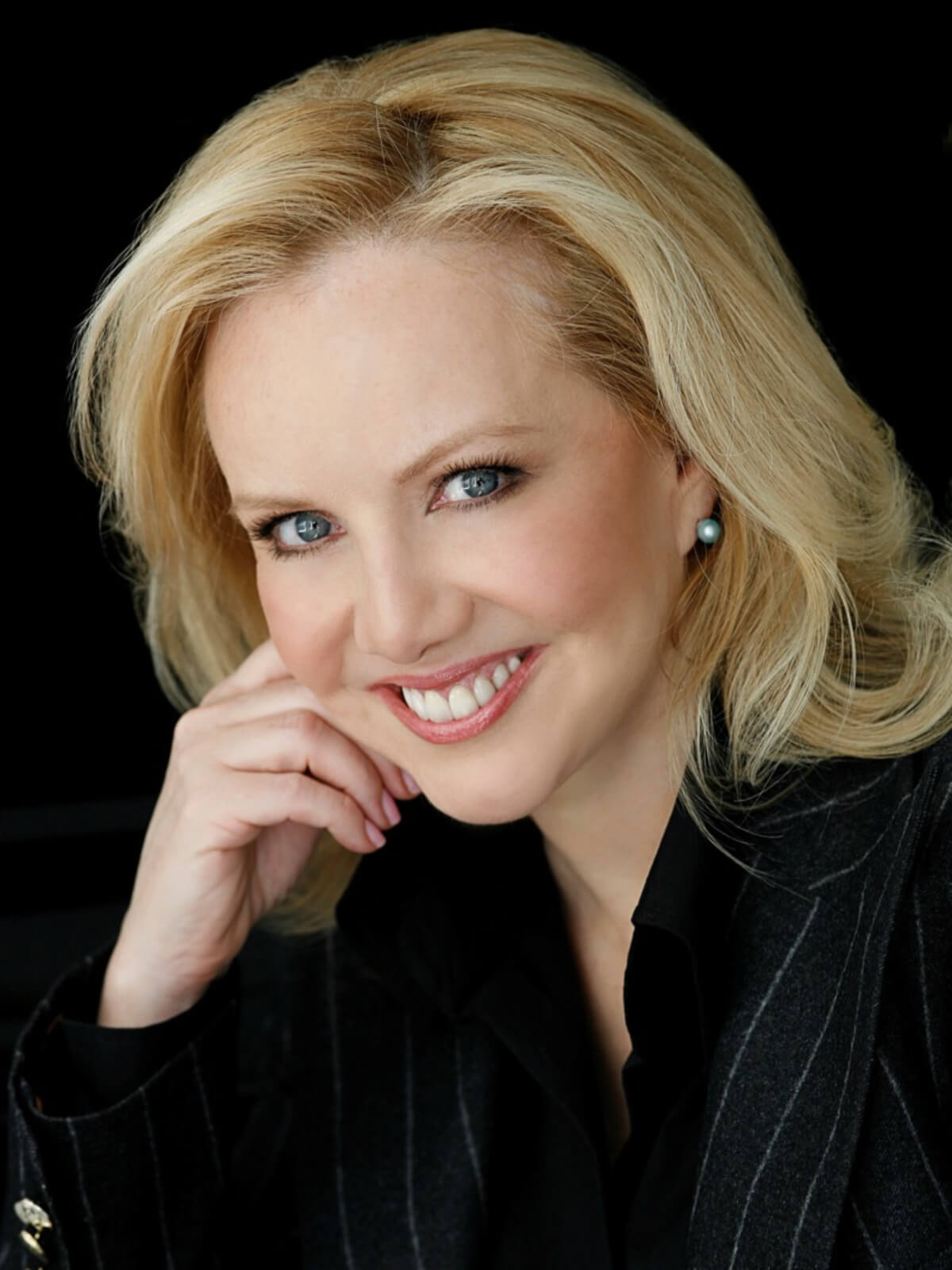 Headshot of Susan Stroman. She is wearing a pinstriped black suit smiling to camera with head resting on upstage hand.