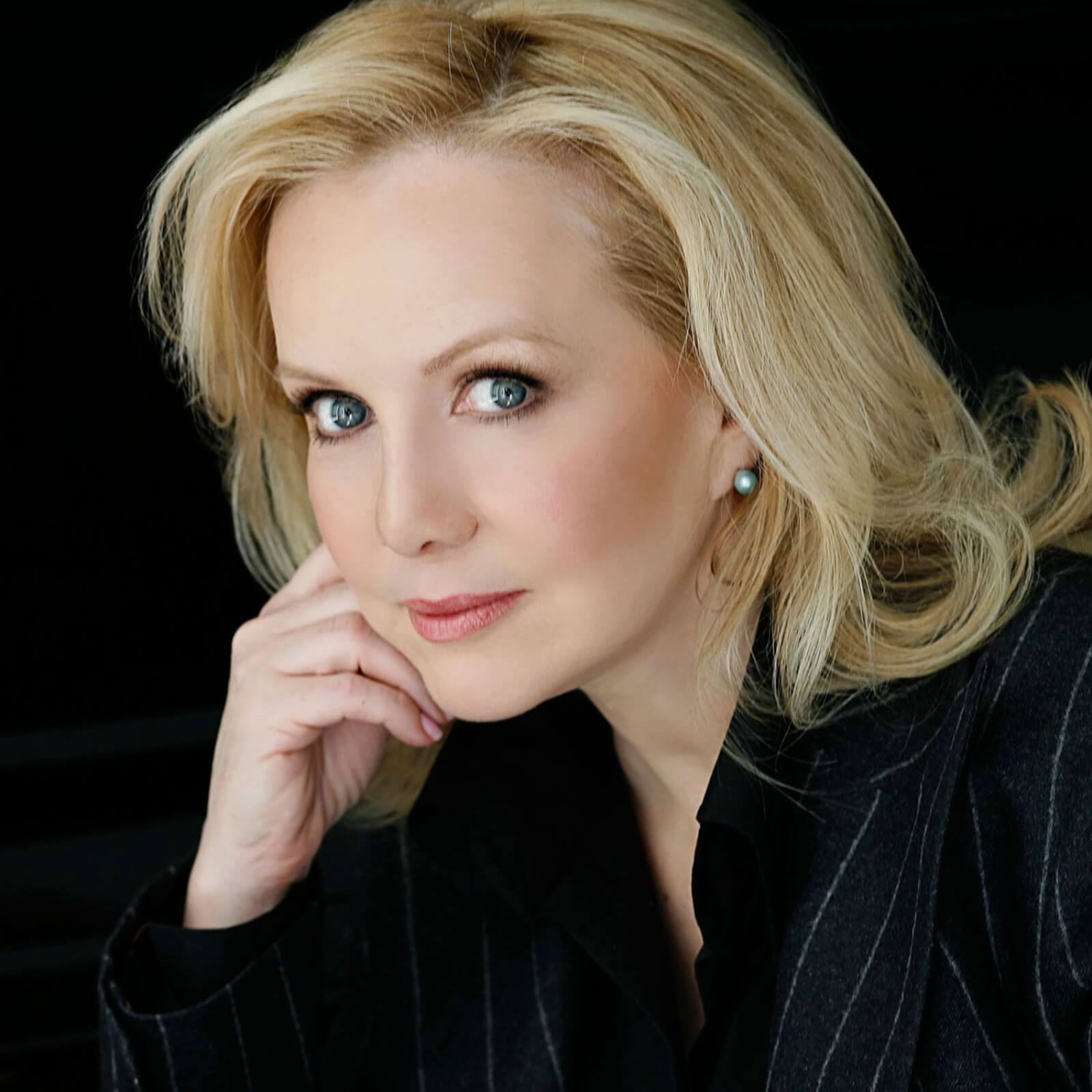 Headshot of Susan Stroman. She is wearing a pinstriped suit with chin resting on upstage hand. This photo is in color.