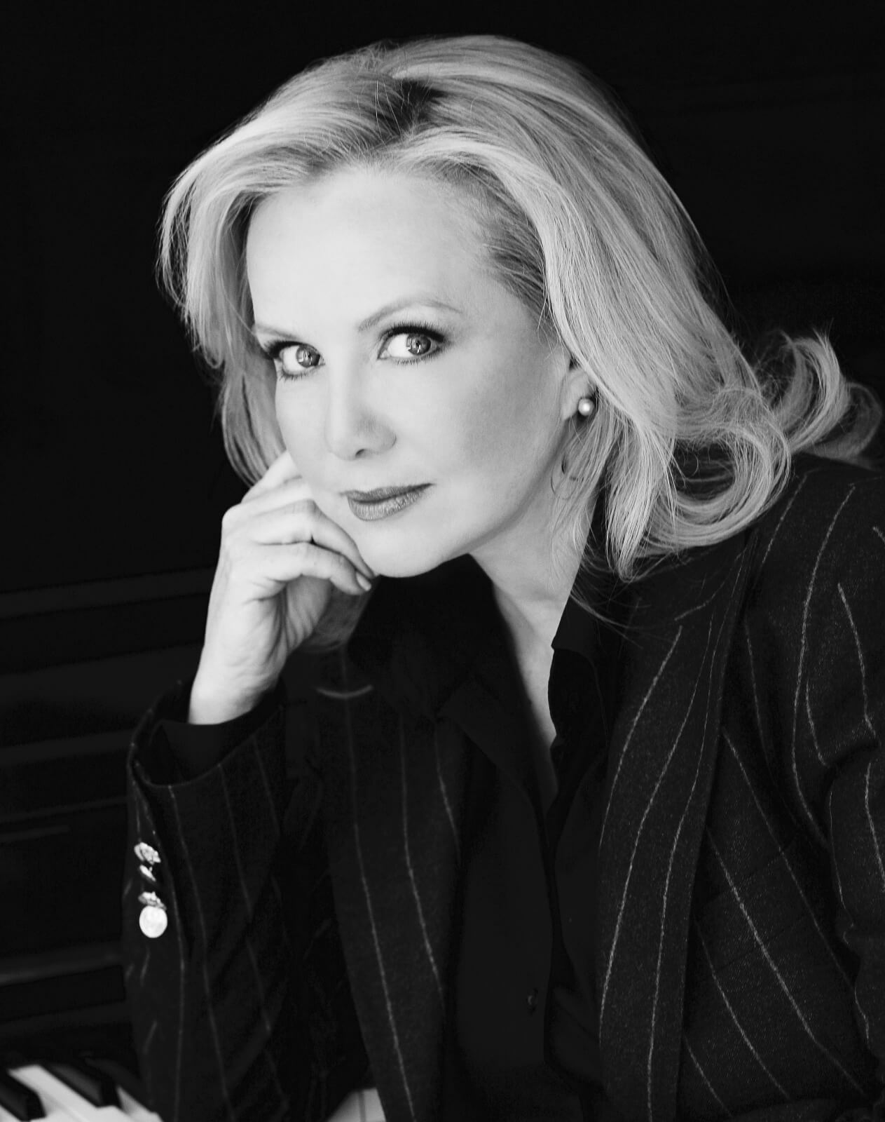 Headshot of Susan Stroman in pinstriped suit with chin resting on upstage hand. This photo is in black and white.