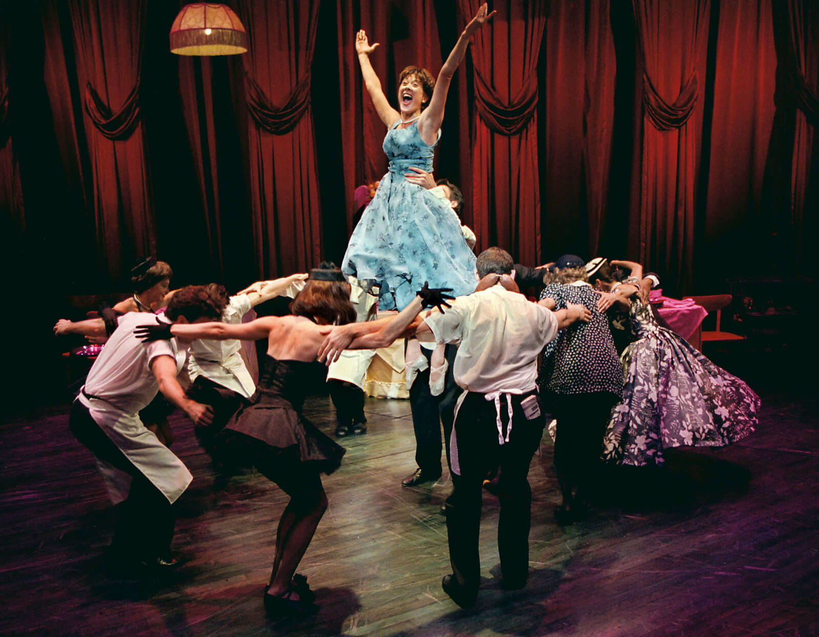 Wife (Karen Ziemba) wearing a blue dress is lifted with outstretched arms while surrounded by the full company.