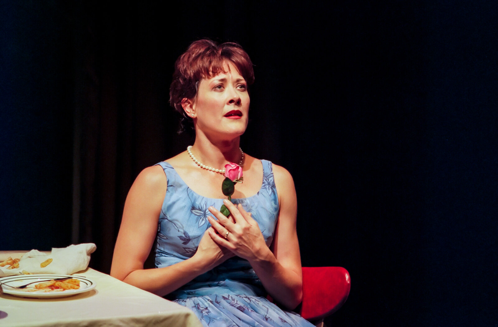 """Wife (Karen Ziemba) clutches a pink rose in the final moment of """"Did You Move?"""" from Contact."""