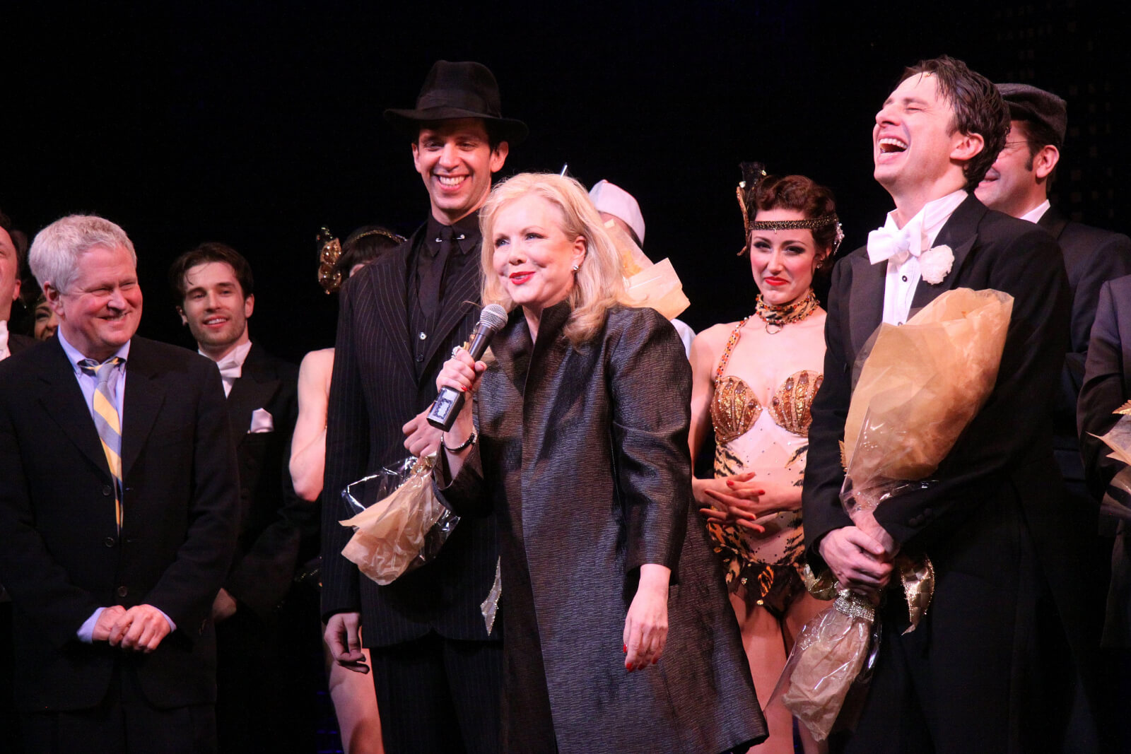 Susan Stroman at the opening night curtain call of Bullets Over Broadway, standing with a microphone and flanked by cast, including Nick Cordero and Zach Braff.
