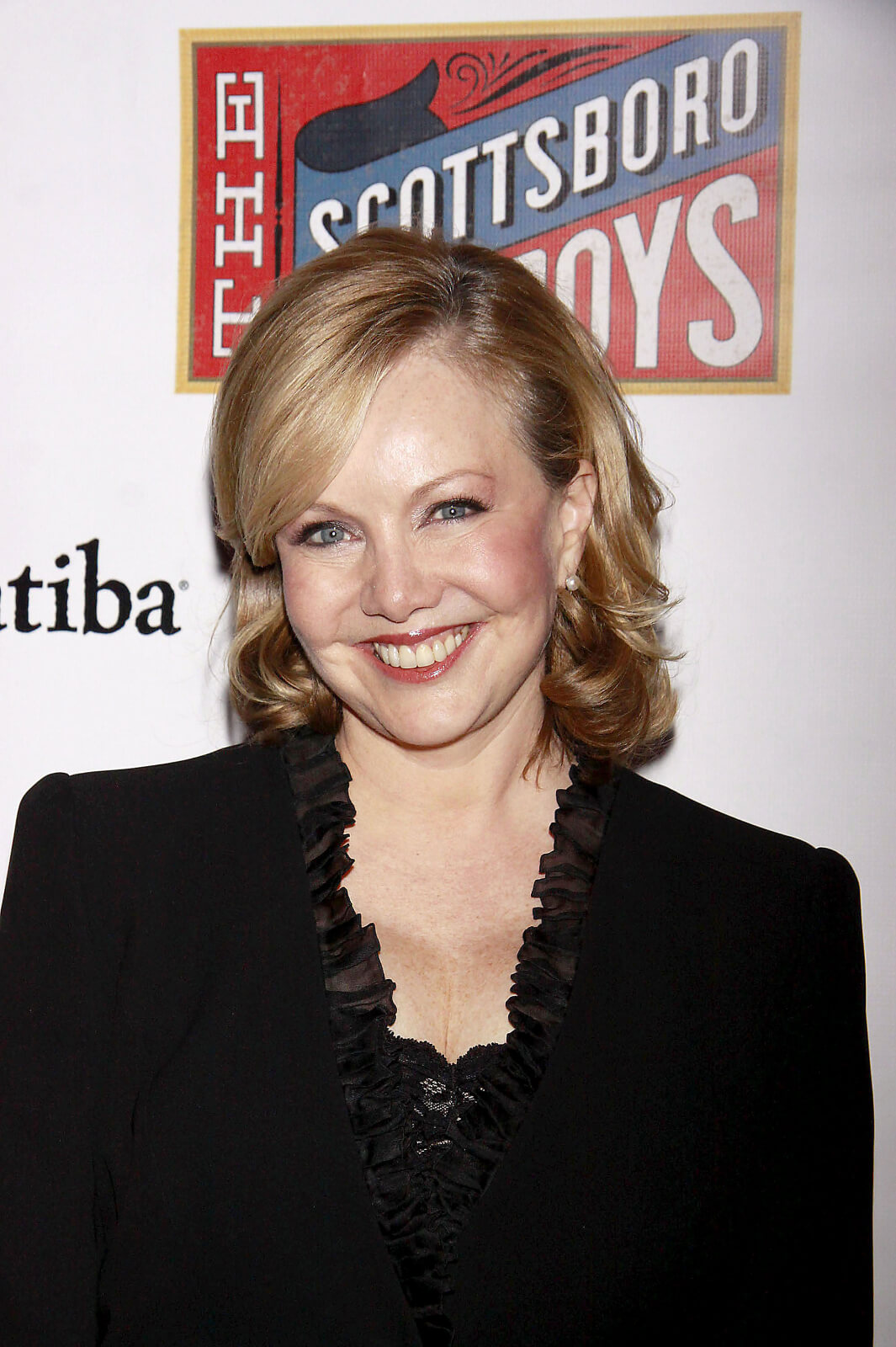 Susan Stroman, dressed in a black suit, at The Scottsboro Boys Opening Night, logo of show is shown on the step-and-repeat wall behind her.