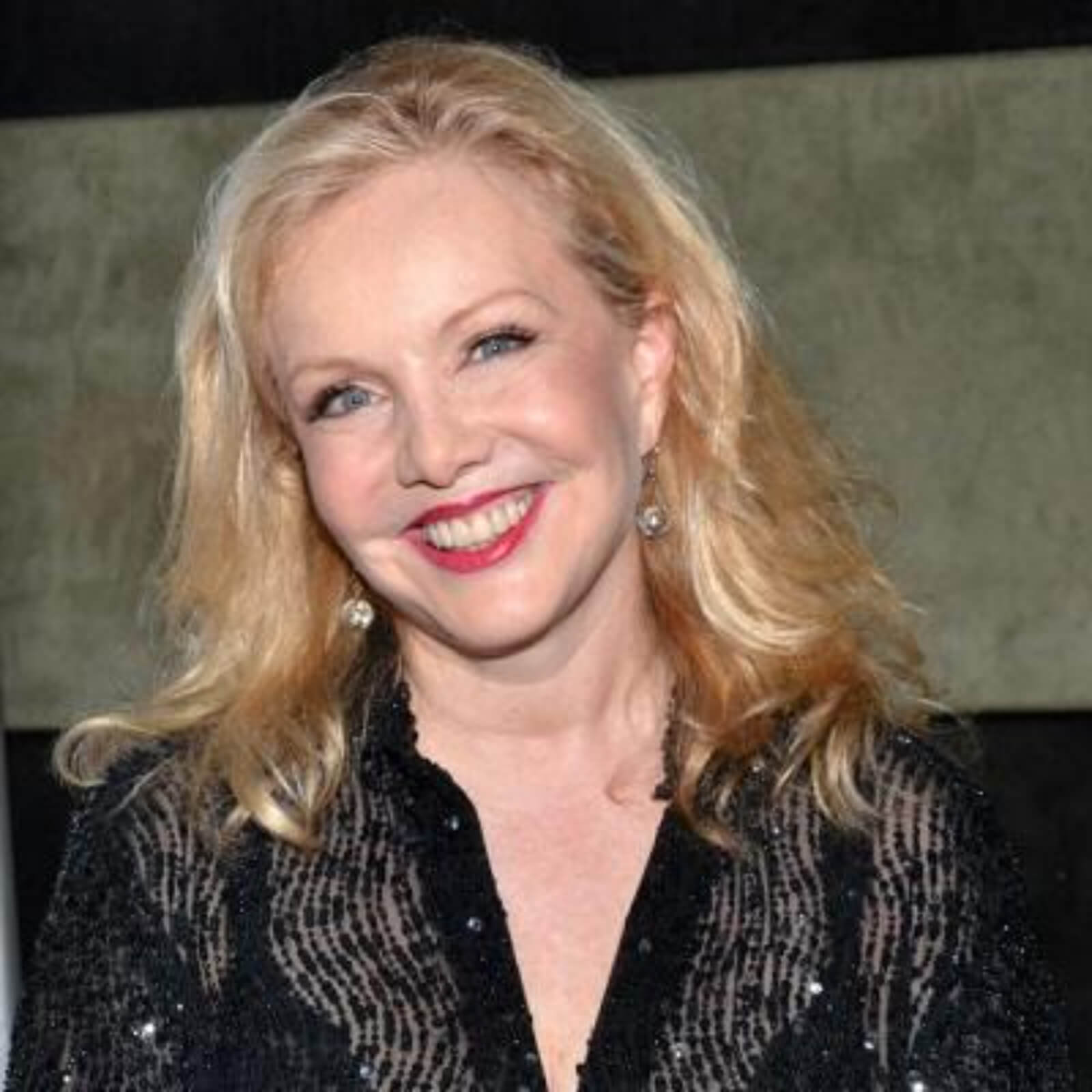 Headshot of Susan Stroman in a sparkly black shirt and beaming smile.