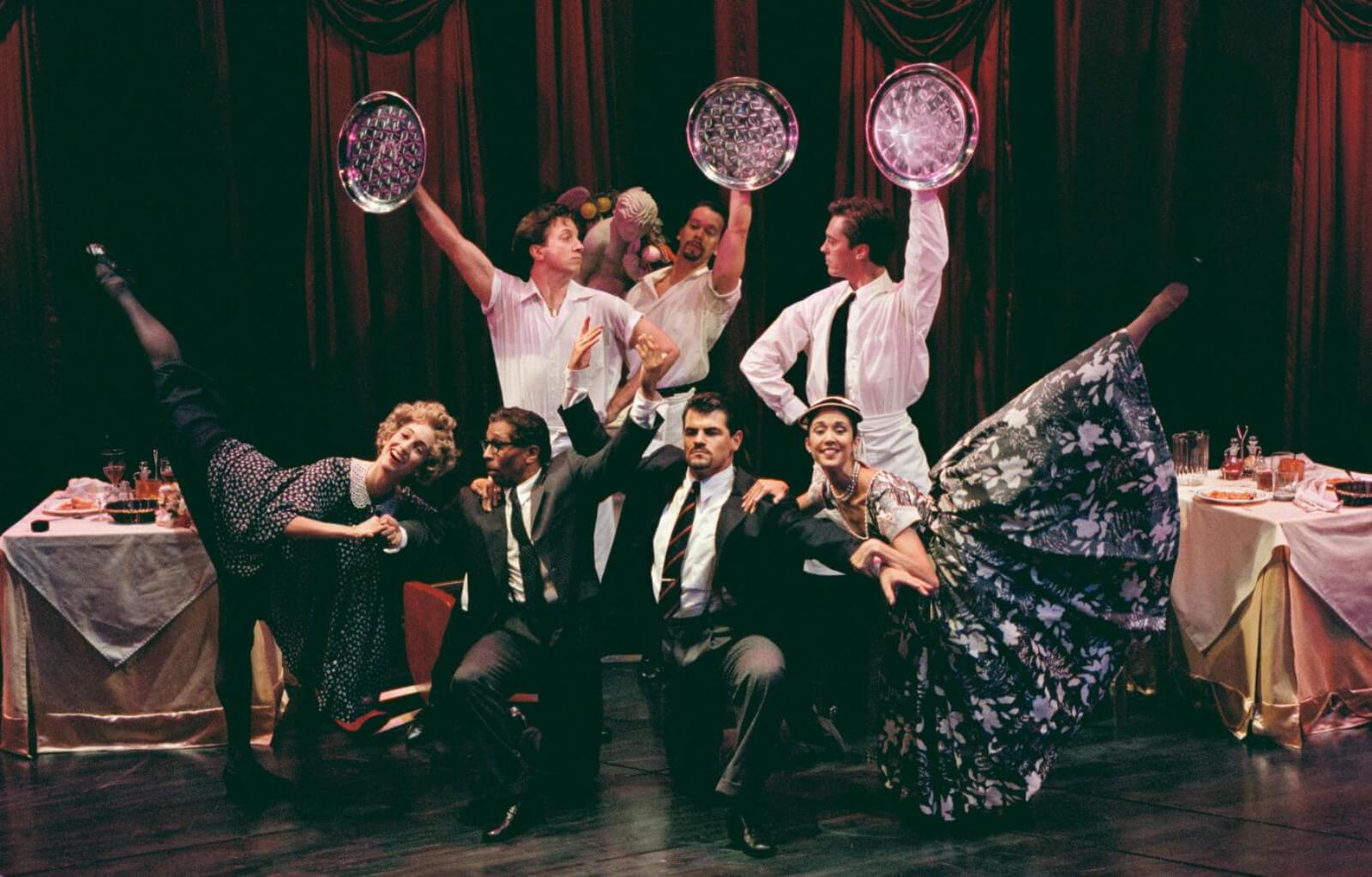 """Nina Goldman, Tomé Cousin, Stacey Todd Holt, Robert Wersinger, Peter Gregus, Scott Taylor, and Dana Stackpole in """"Did You Move?"""" from Contact. They are all dressed like waiters and diners."""