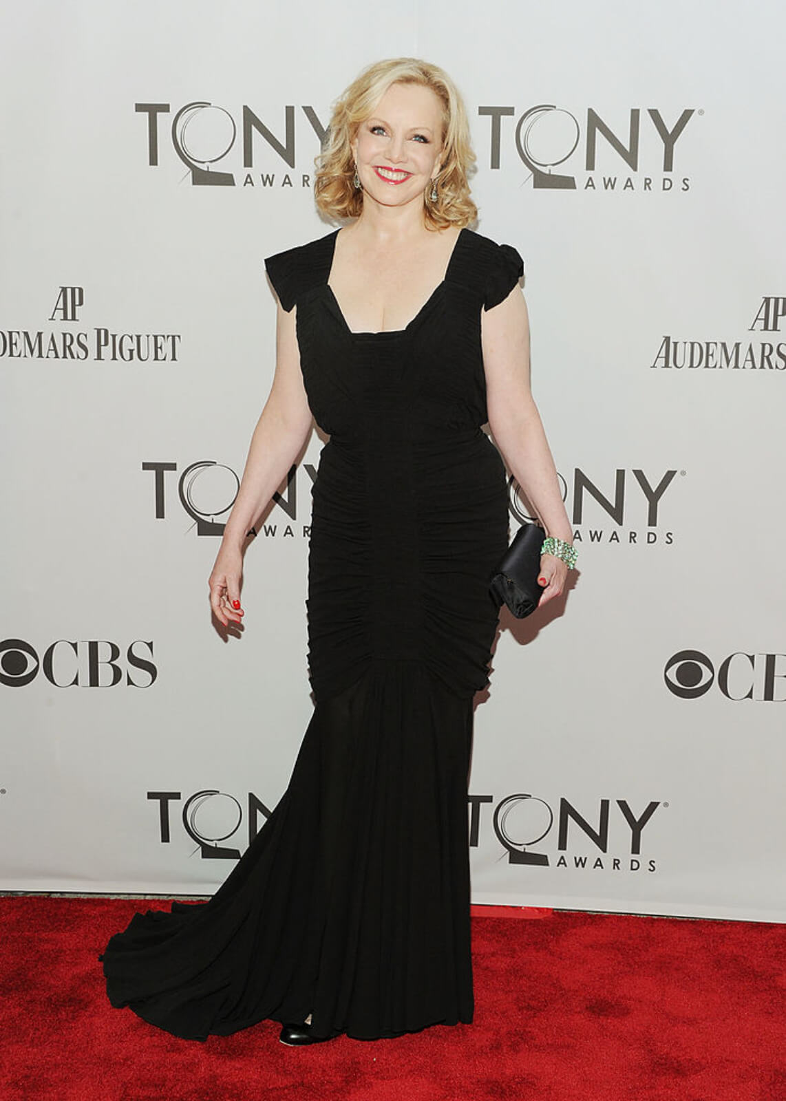 Portrait of Susan Stroman on the red carpet at the Tony Awards in a black dress, smiling with a clutch in her left hand.